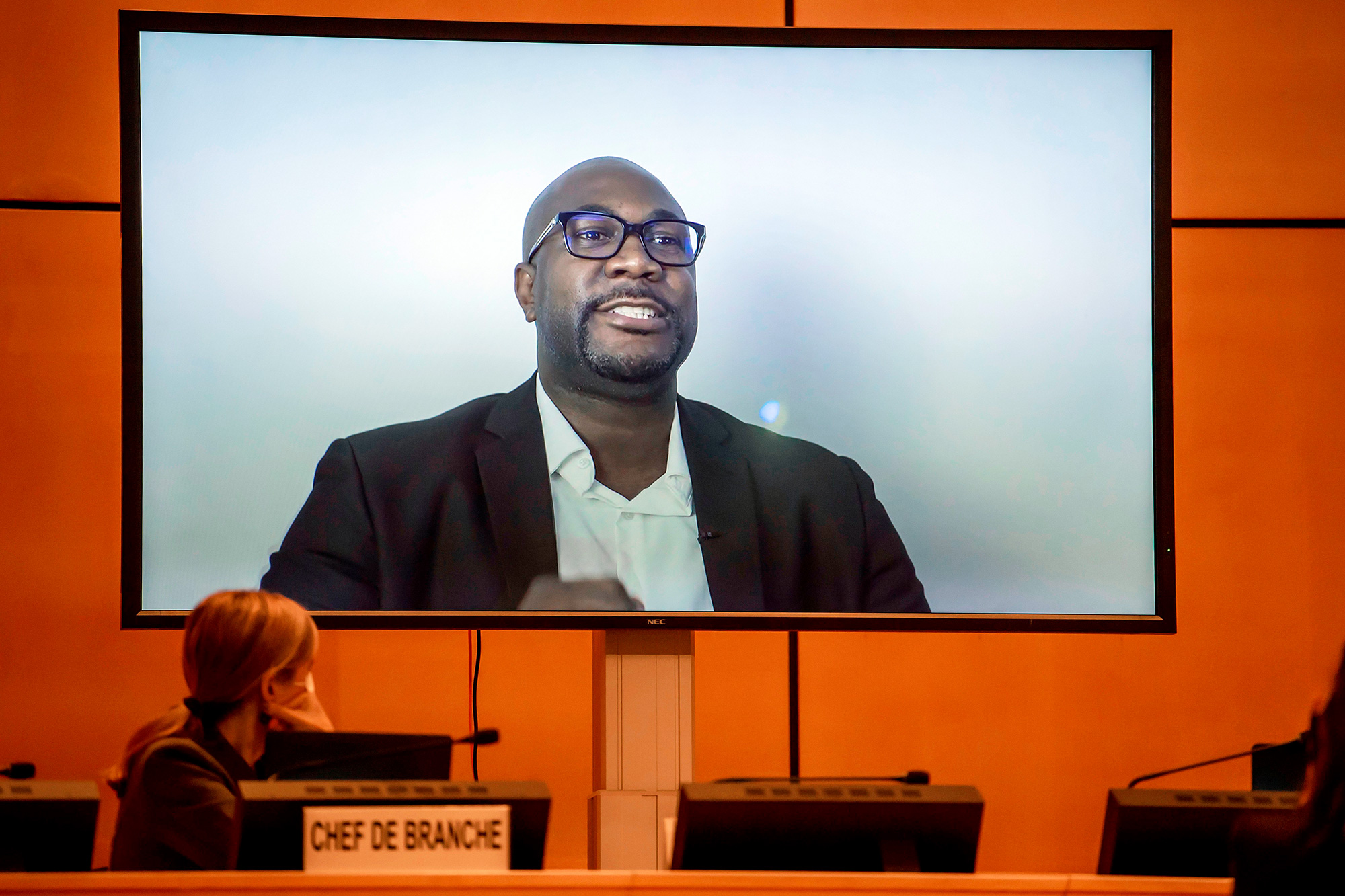"A TV screen displays George Floyd's brother, Philonise Floyd speaking via video message during an urgent debate on ""systemic racism"" in the United States and beyond at the Human Rights Council on June 17, 2020 in Geneva"