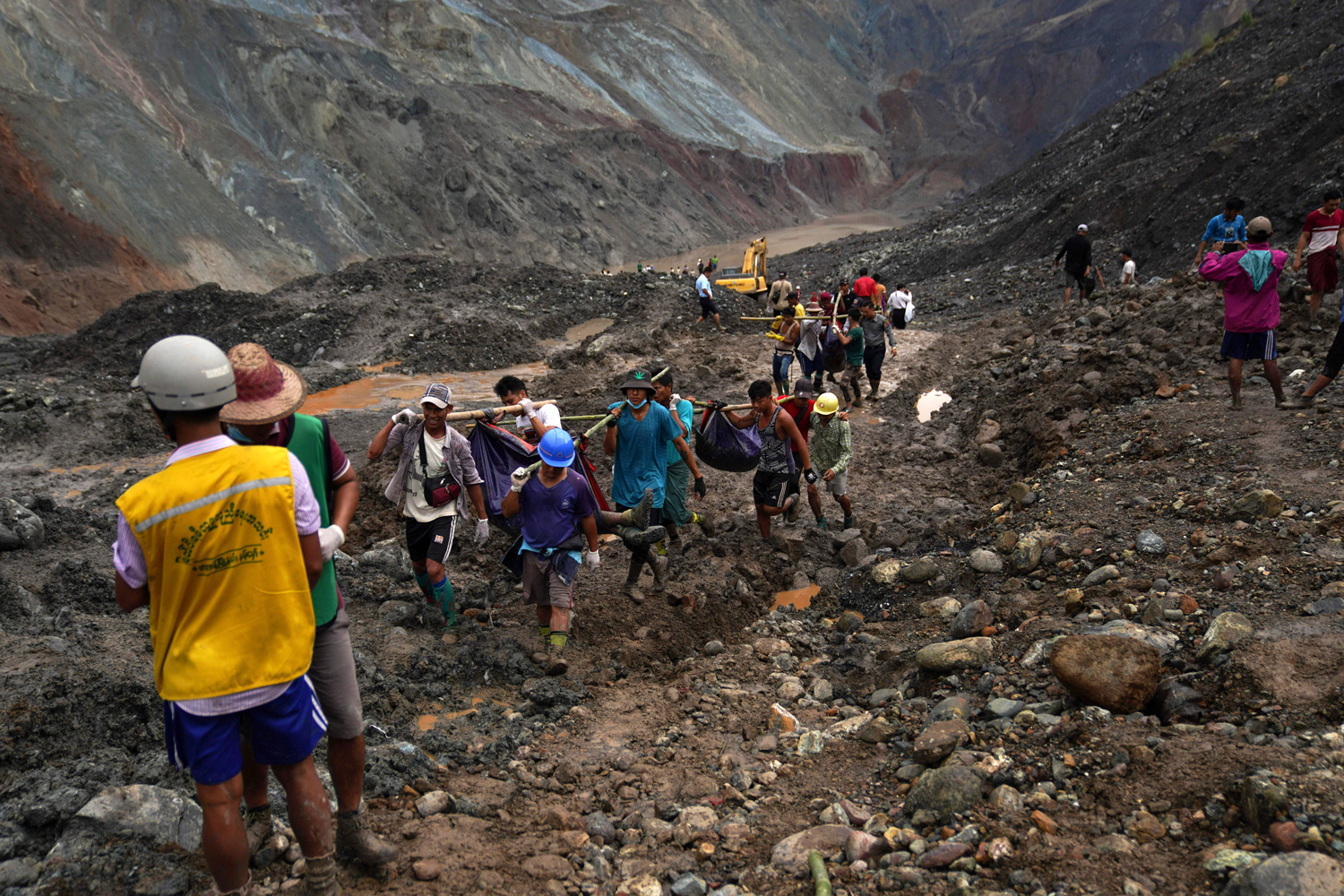 Rescuers recover bodies near the landslide area in the jade mining site in Hpakhant
