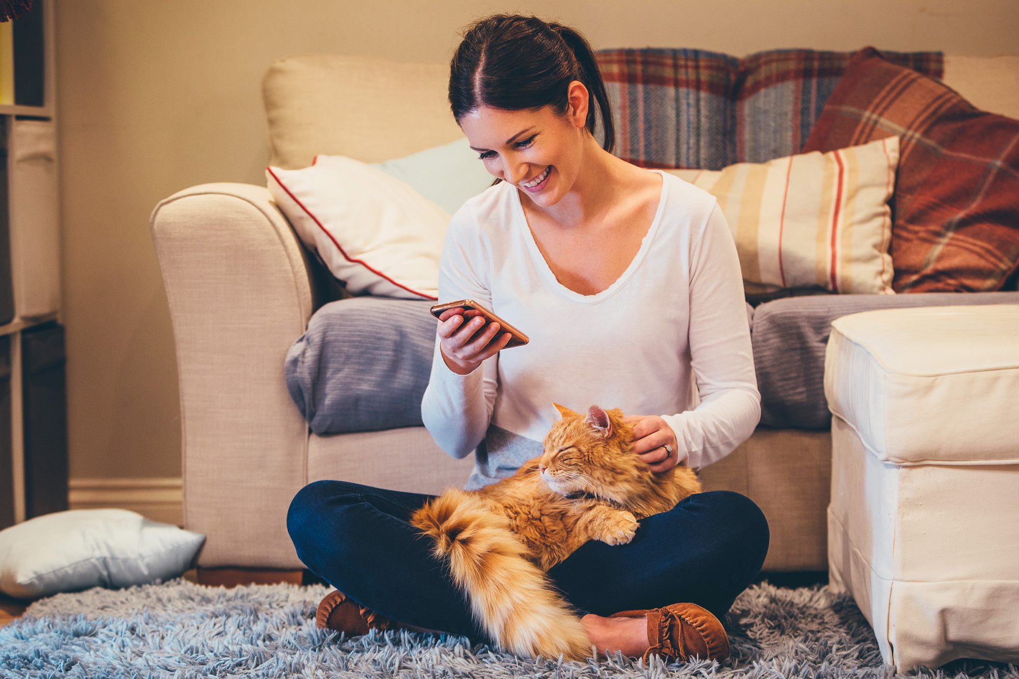 Woman sitting with cat on phone