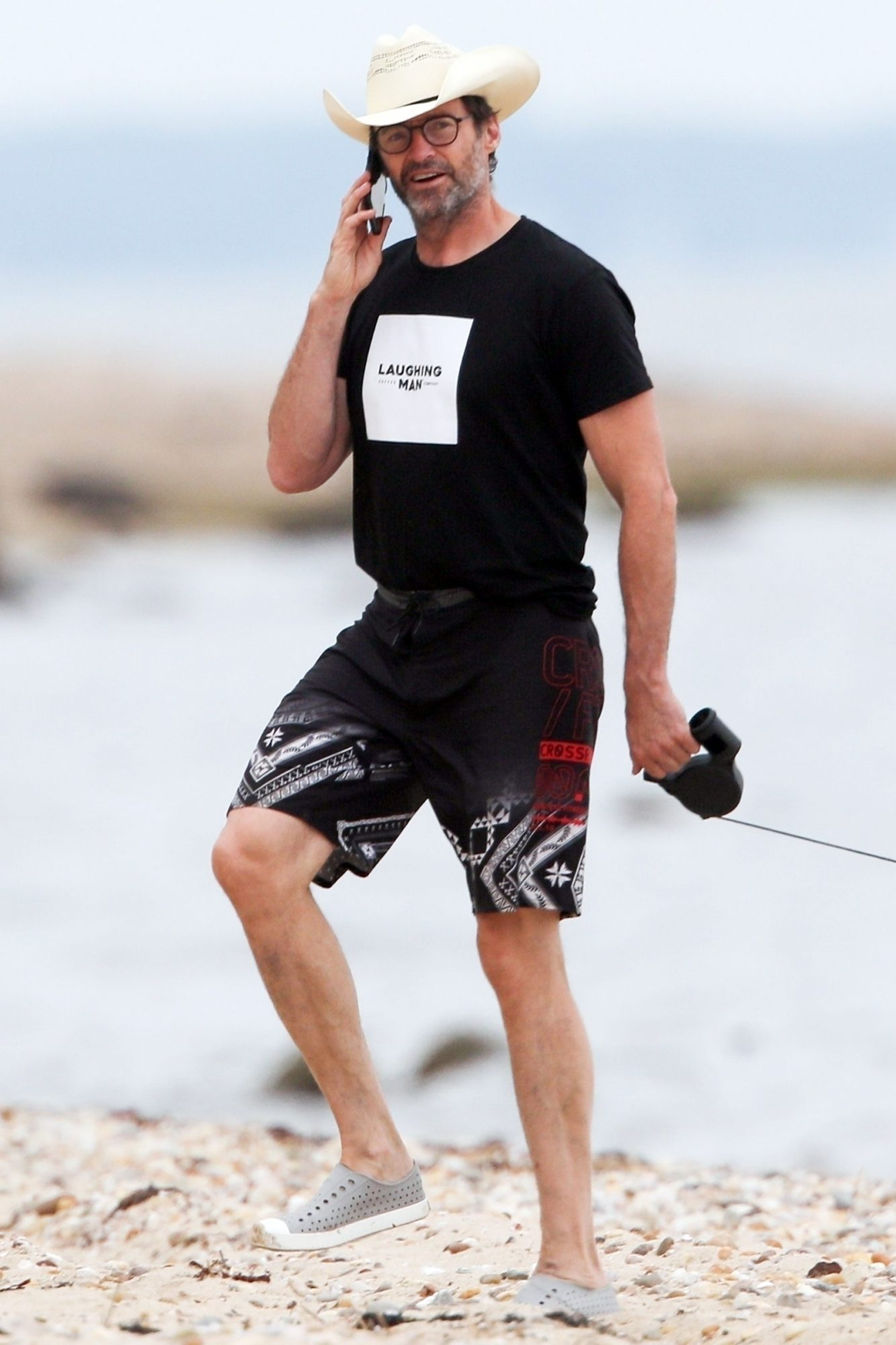 Hugh Jackman chatting on the phone while walking his dogs in The Hamptons