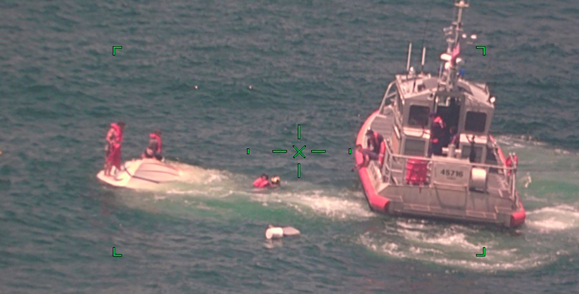 members of the Coast Guard rescue a family of four, from a vessel taking on water 17 miles south of Southwest Pass near Venice, La