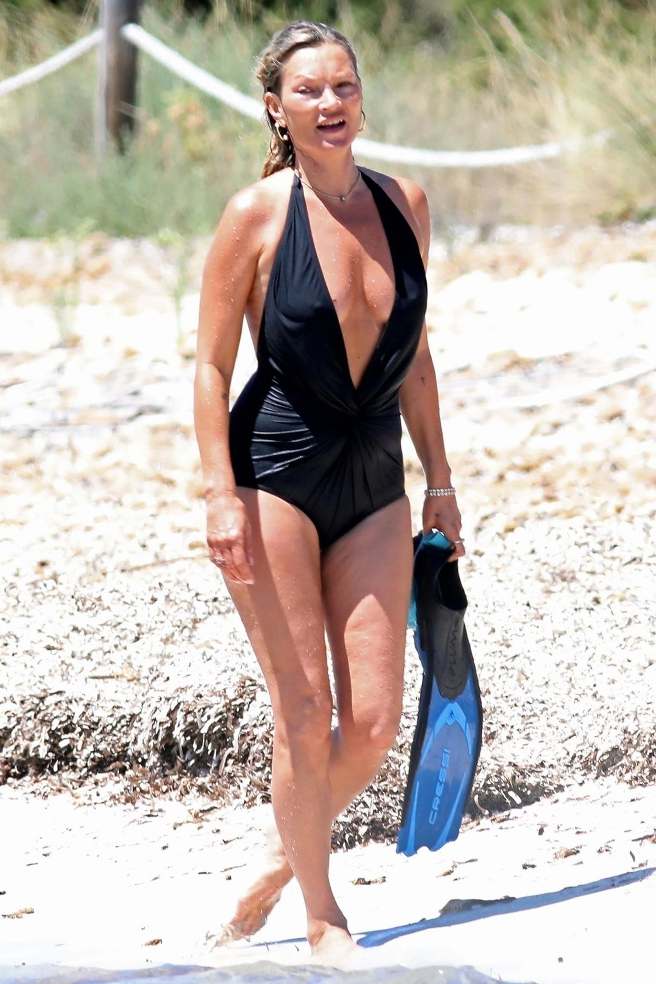 Kate Moss looks spectacular in a black halter neck swimsuit