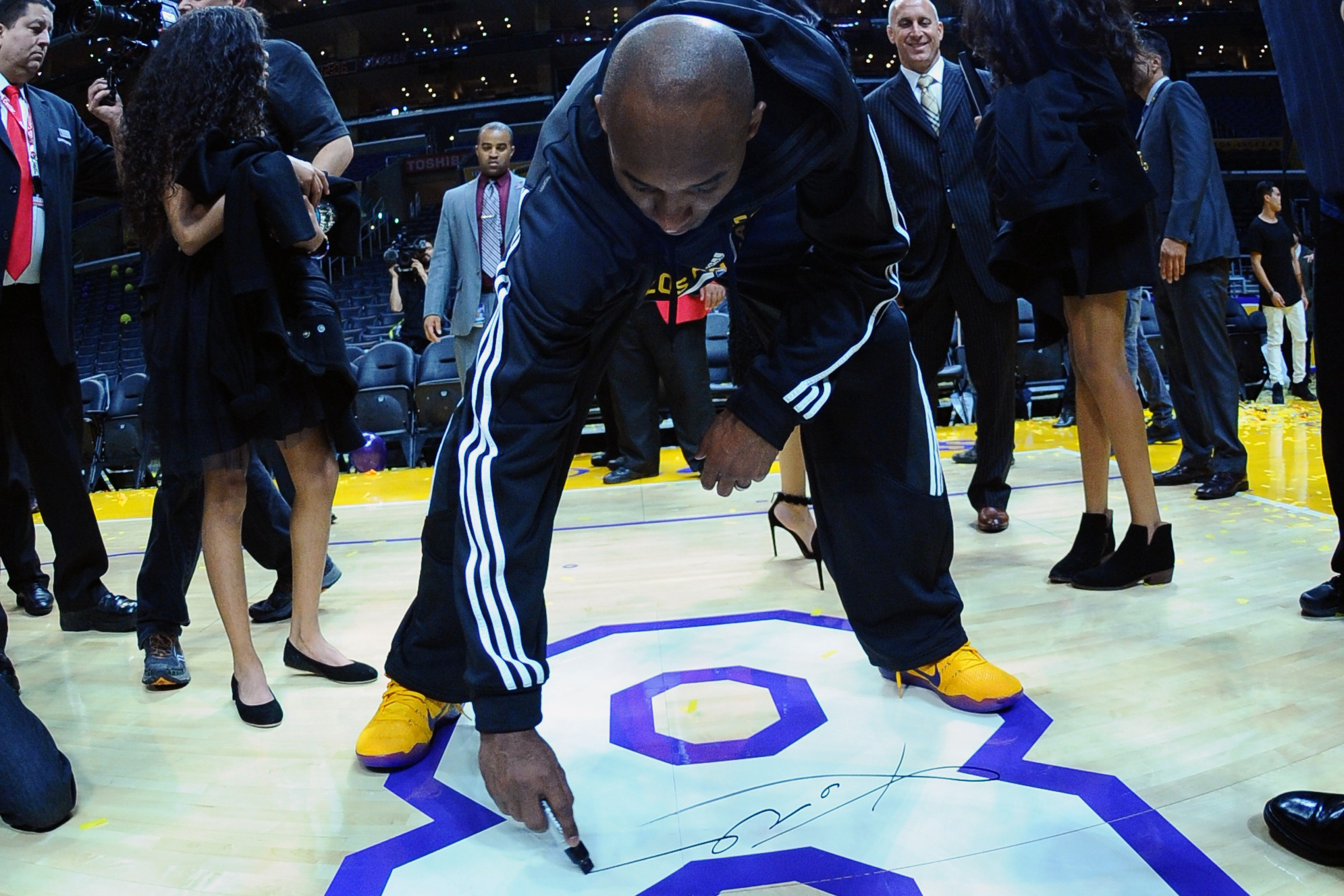 Kobe Bryant #24 of the Los Angeles Lakers autographs the floor after the game against the Utah Jazz at STAPLES Center on April 13, 2016 in Los Angeles, California