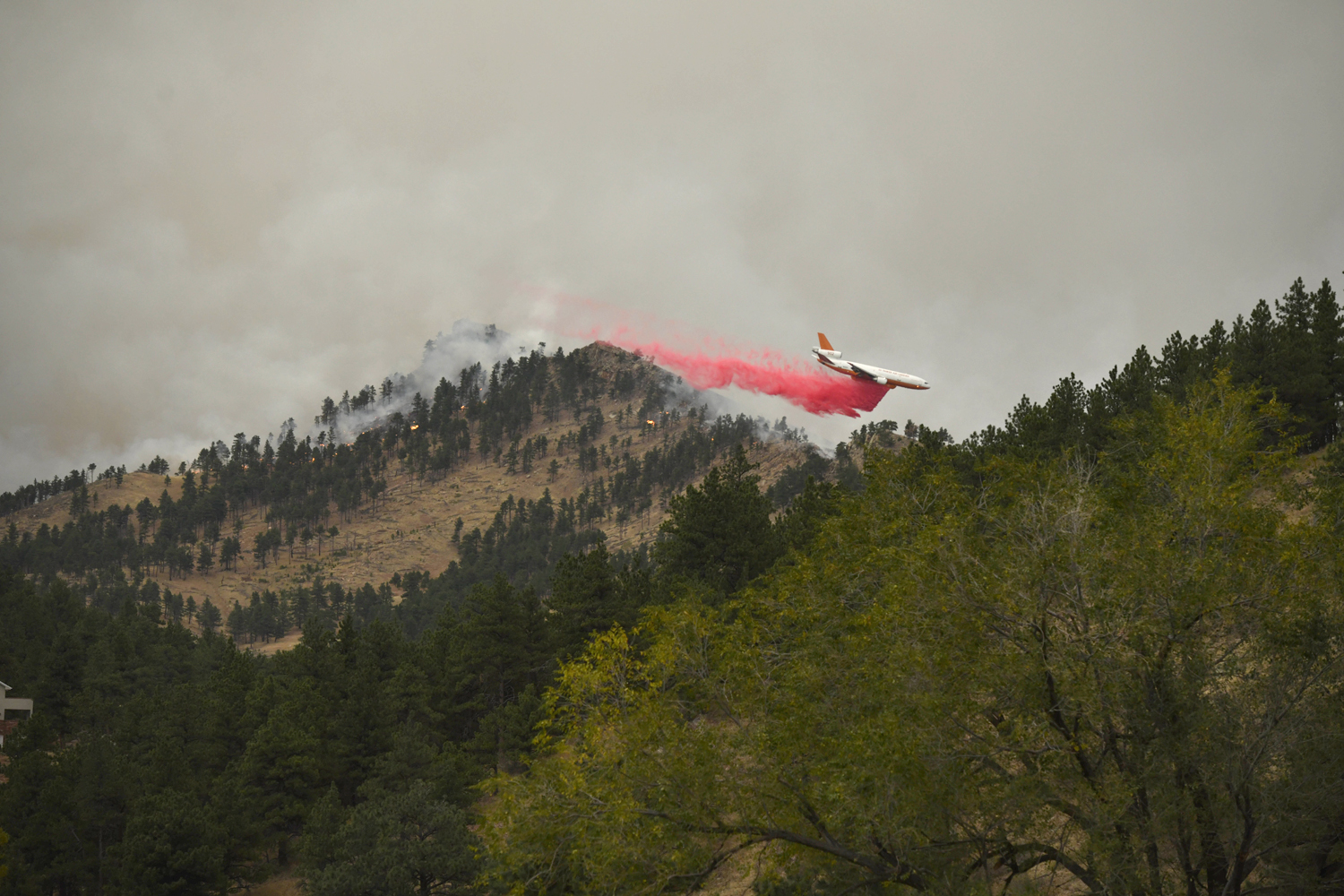 A slurry bomber drops retardant over the CalWood fire near Buckingham Park northwest of Boulder