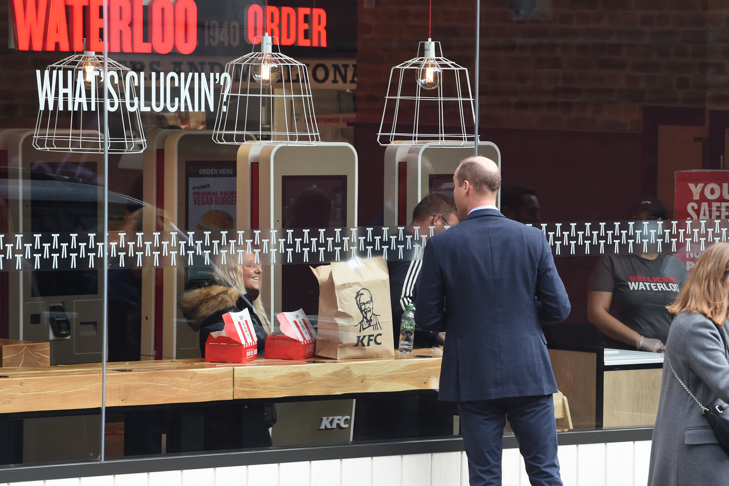 Prince William, Duke of Cambridge speaks to a member of the public through the window of a KFC