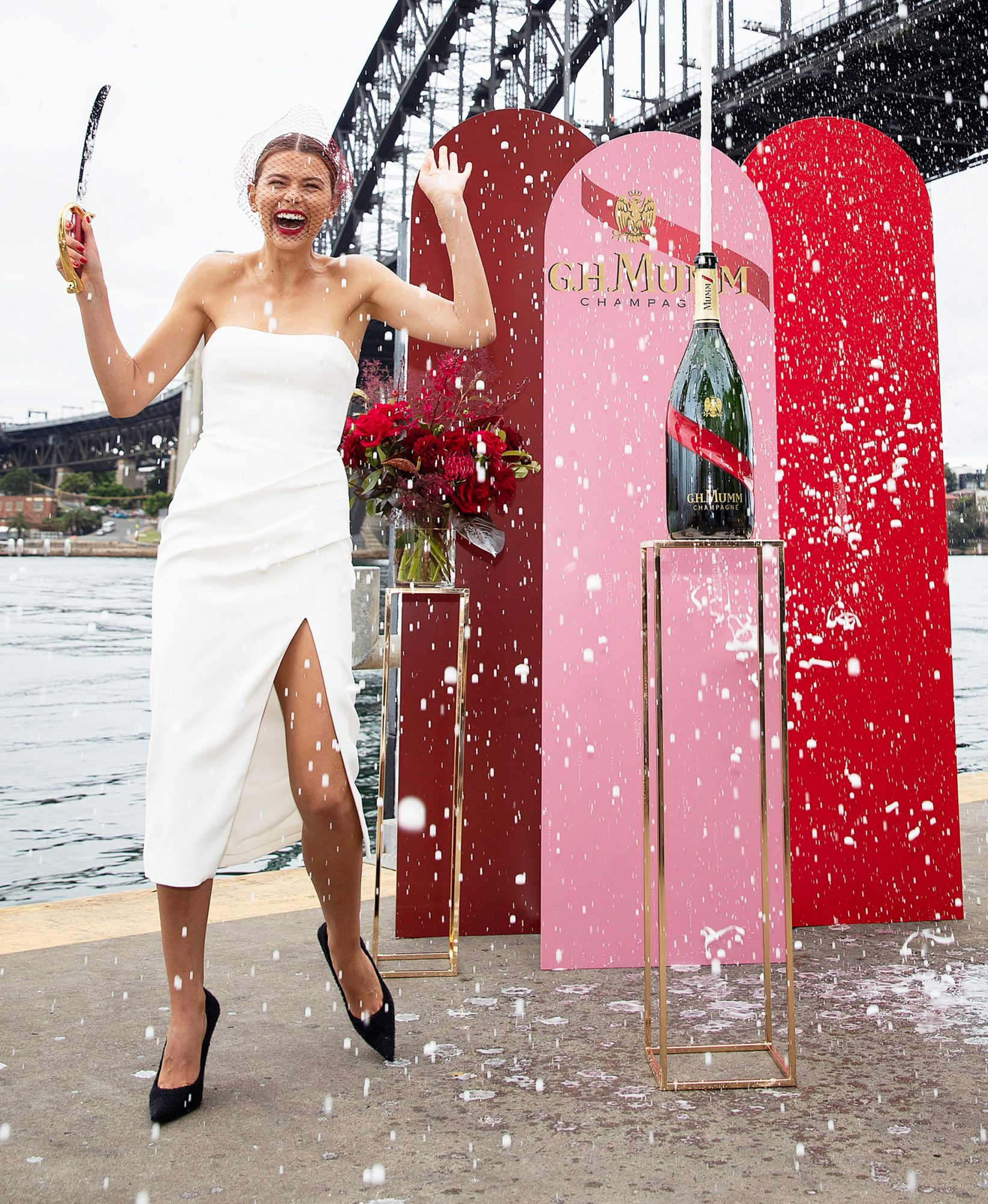 Georgia Fowler performs a 'tap tap' moment on a bottle of G.H. Mumm during the launch of G.H. Mumm Melbourne Cup Carnival celebrations at Pier One Hotel on October 28, 2020