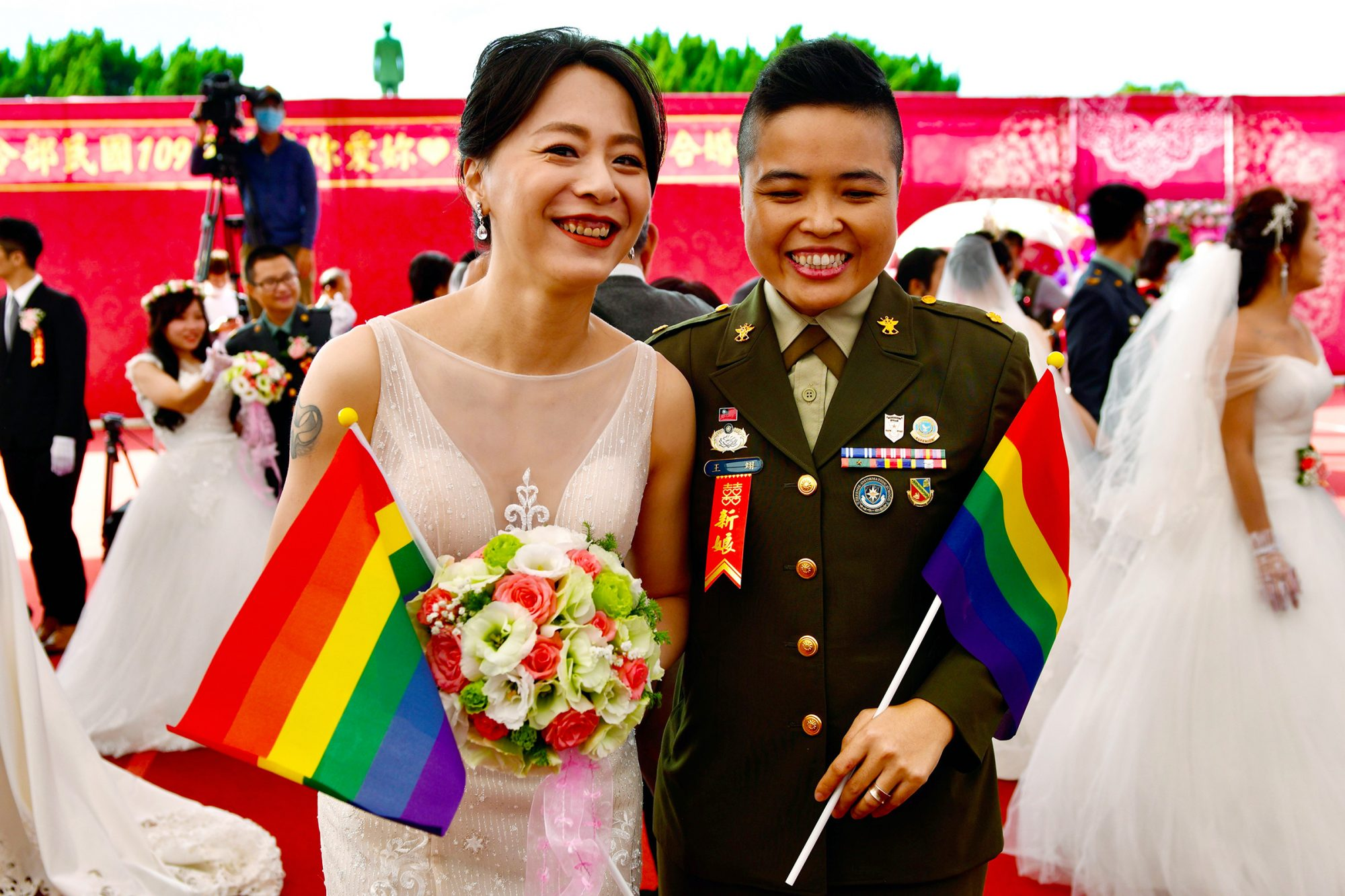Newly-wedded same-sex couple Yi Wang (R) and Yumi Meng pose for a photograph during a mass wedding at Taiwan's Army Command Headquarters