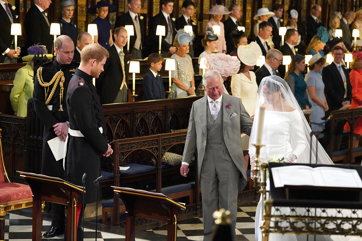 Prince Harry looks at his bride, Meghan Markle, as she arrives accompanied by Prince Charles, Prince of Wales during their wedding