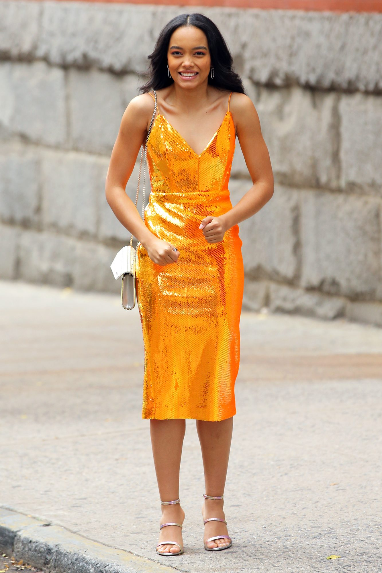 Actress Whitney Peak wears an orange sparkly cocktail dress filming 'Gossip Girl at Park Avenue Armory in New York City
