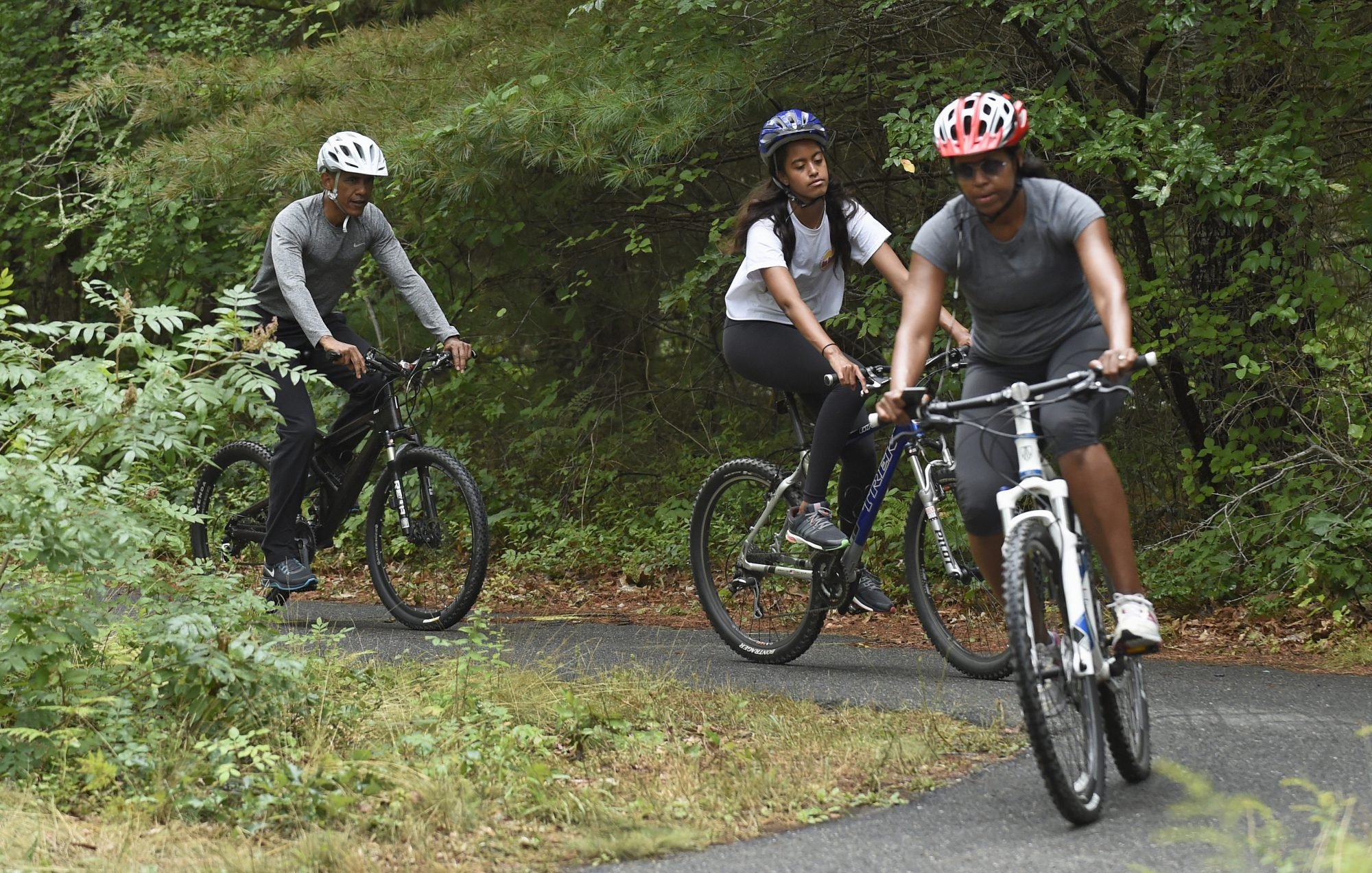 From left: Barack, Malia and Michelle Obama biking on Martha's Vineyard in 2015.