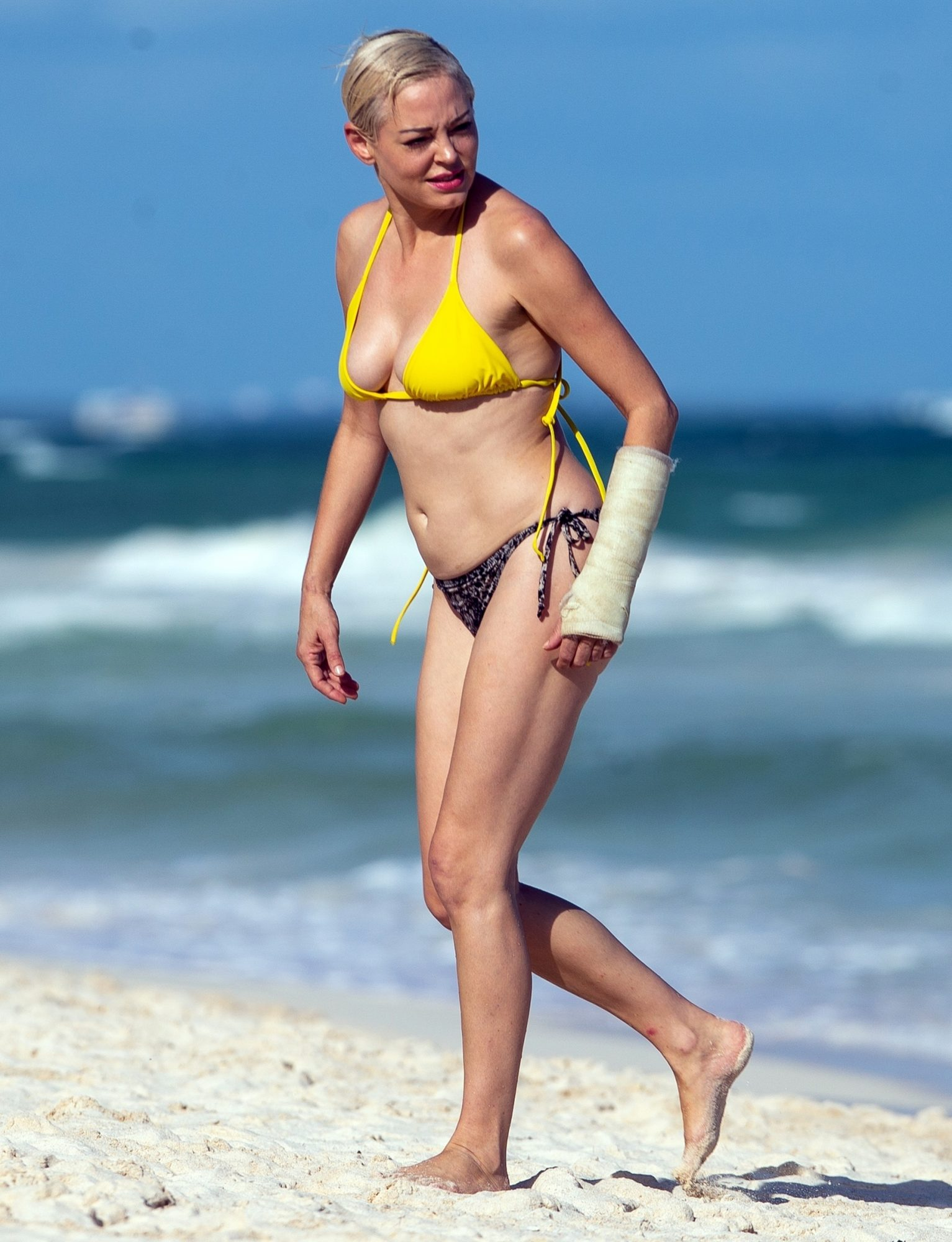 Bikini-clad Rose McGowan dotes on her pet pooch during a trip to Mexico beach