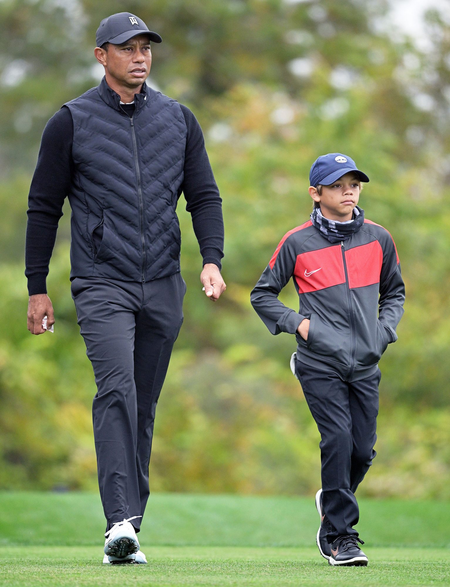 Tiger Woods, left, walks with his son Charlie after hitting their tee shots on the 10th hole during a practice round at the Father Son Challenge golf tournament