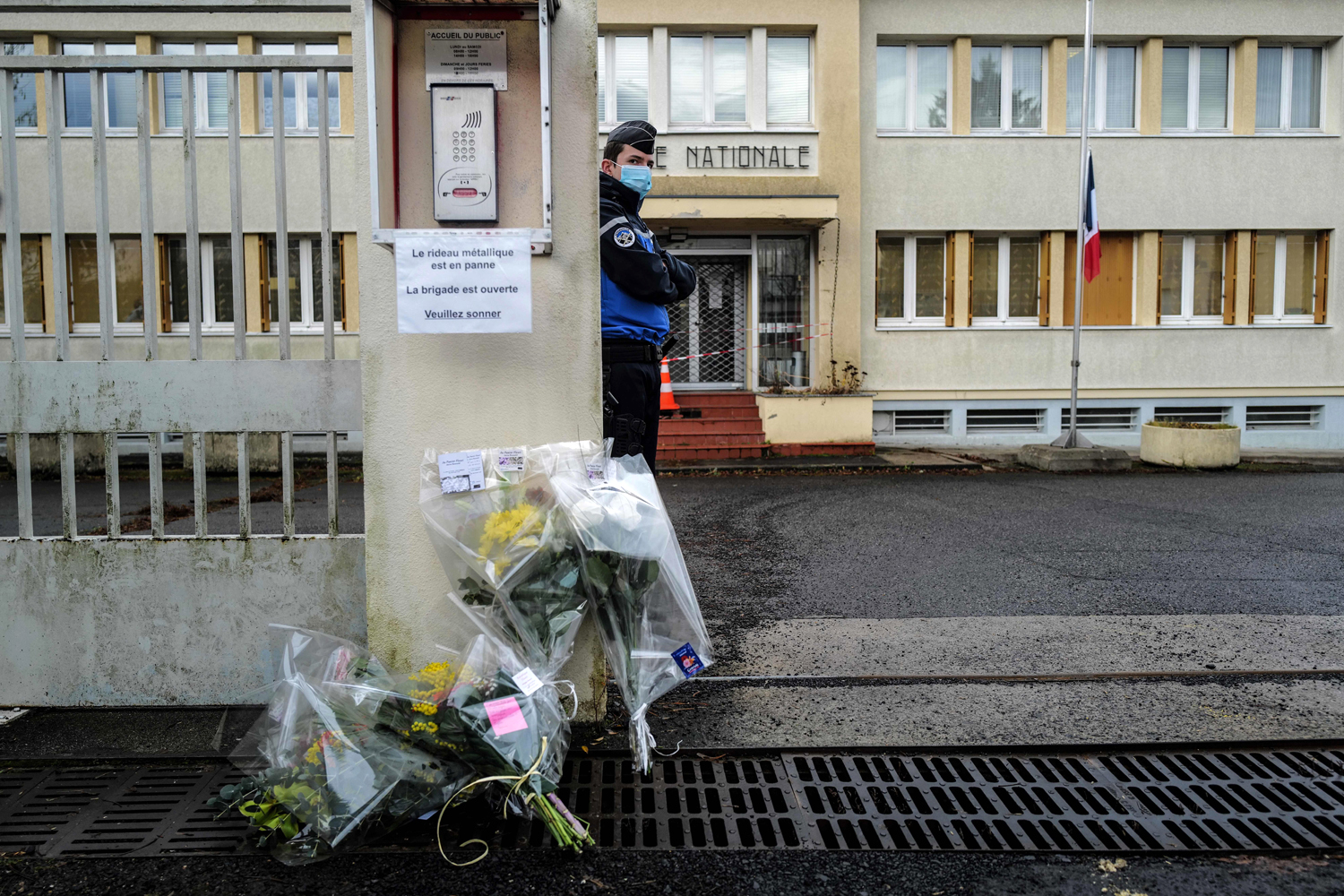 A French Gendarme stands guard next to flowers laid at the entrance of the Gendarmerie