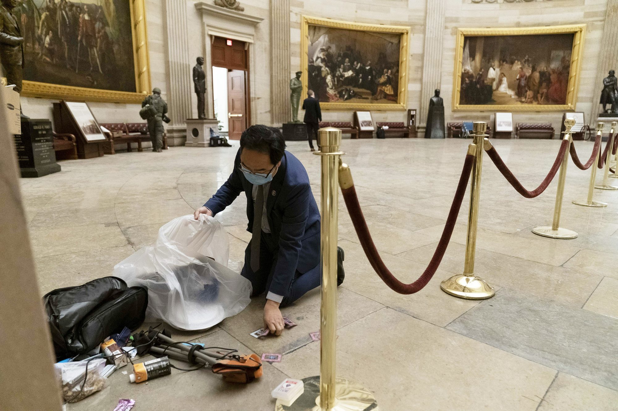 Rep. Andy Kim, D-N.J., cleans up debris and personal belongings strewn across the floor of the Rotunda