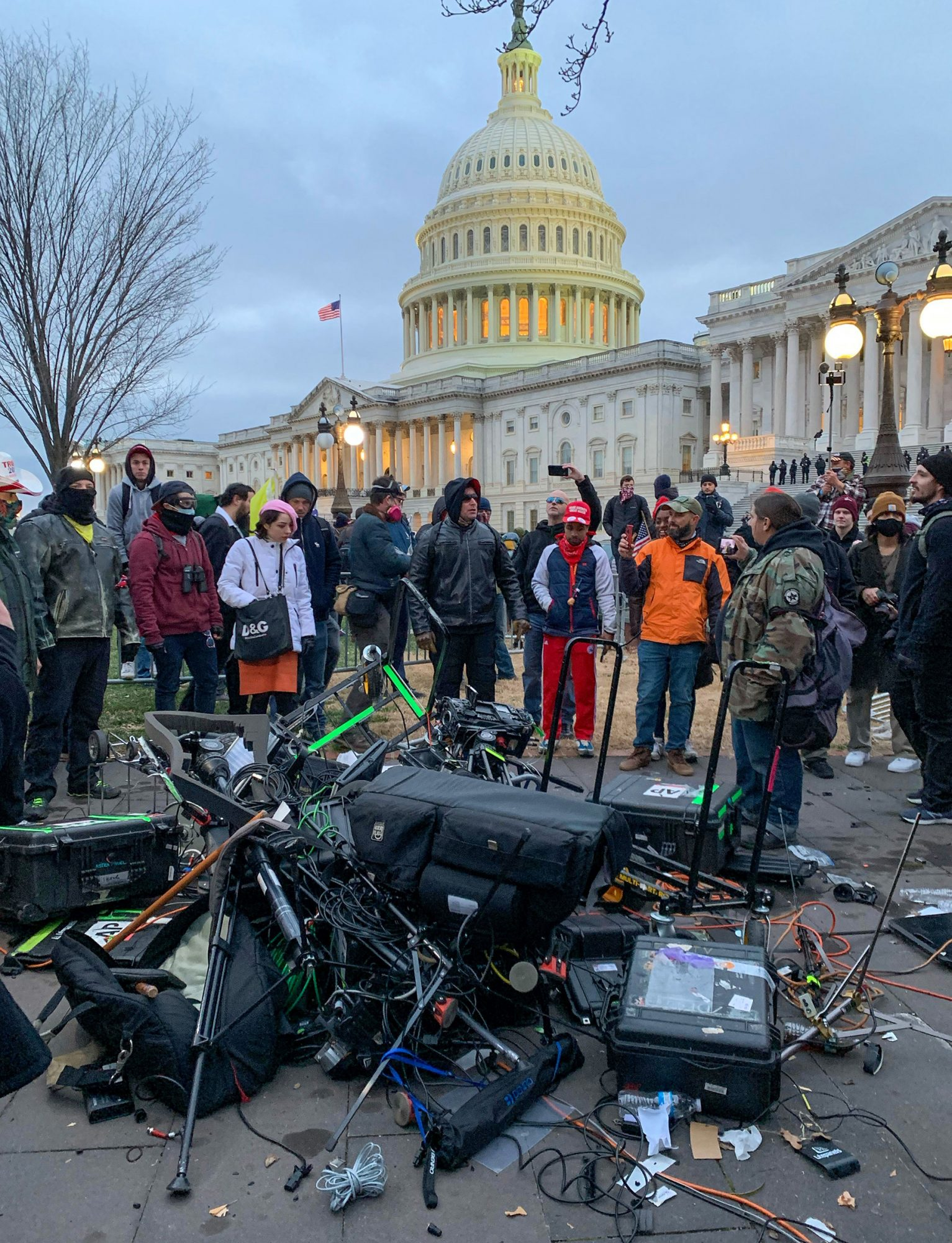 People stand around media equipment destroyed by Trump supporters outside the US Capitol in Washington DC
