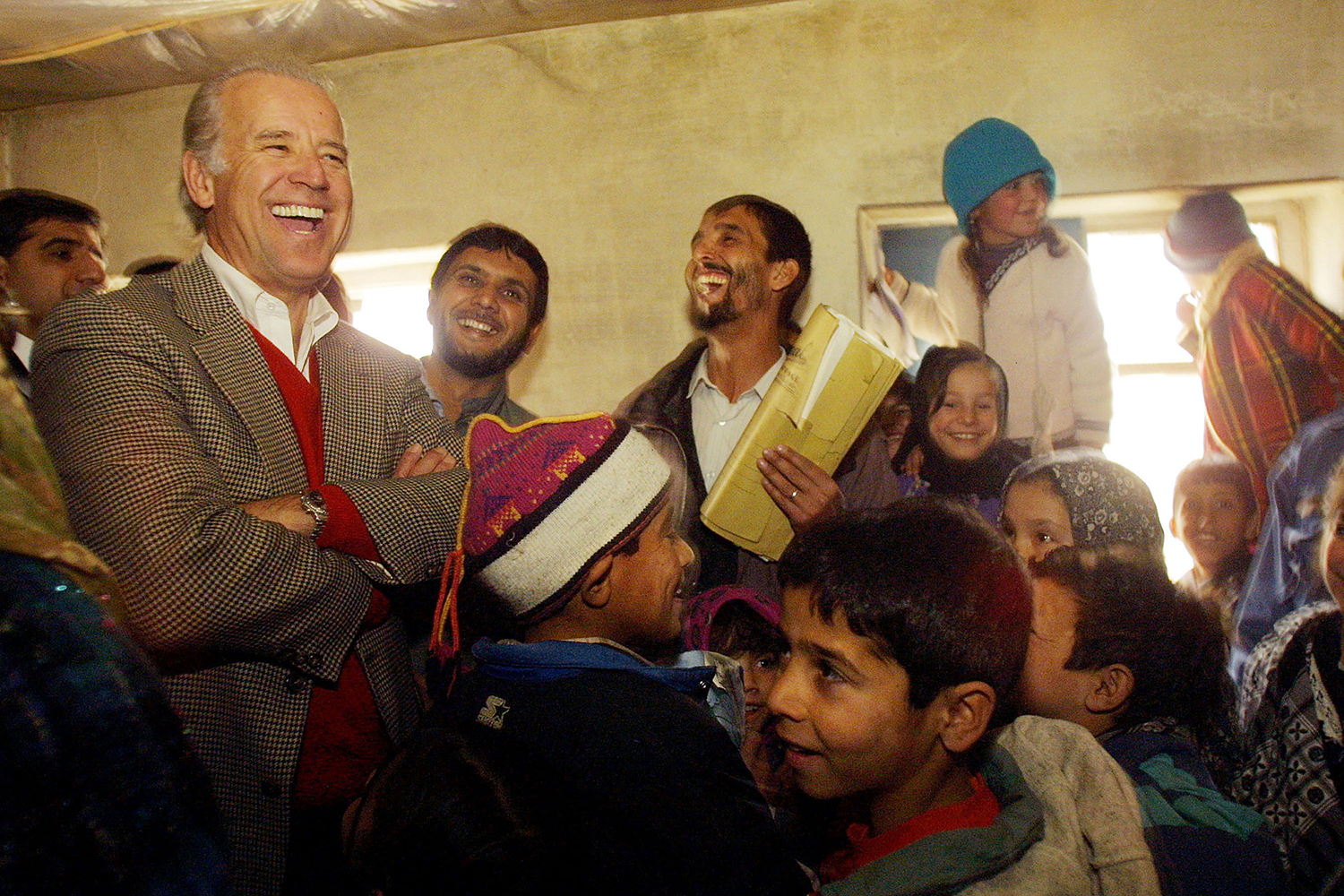 As Foreign Relations Committee Chairman, Biden shares a laugh with Afghan students at Ariana High School during his visit to Kabul, Afghanistan, on Jan. 12, 2002.