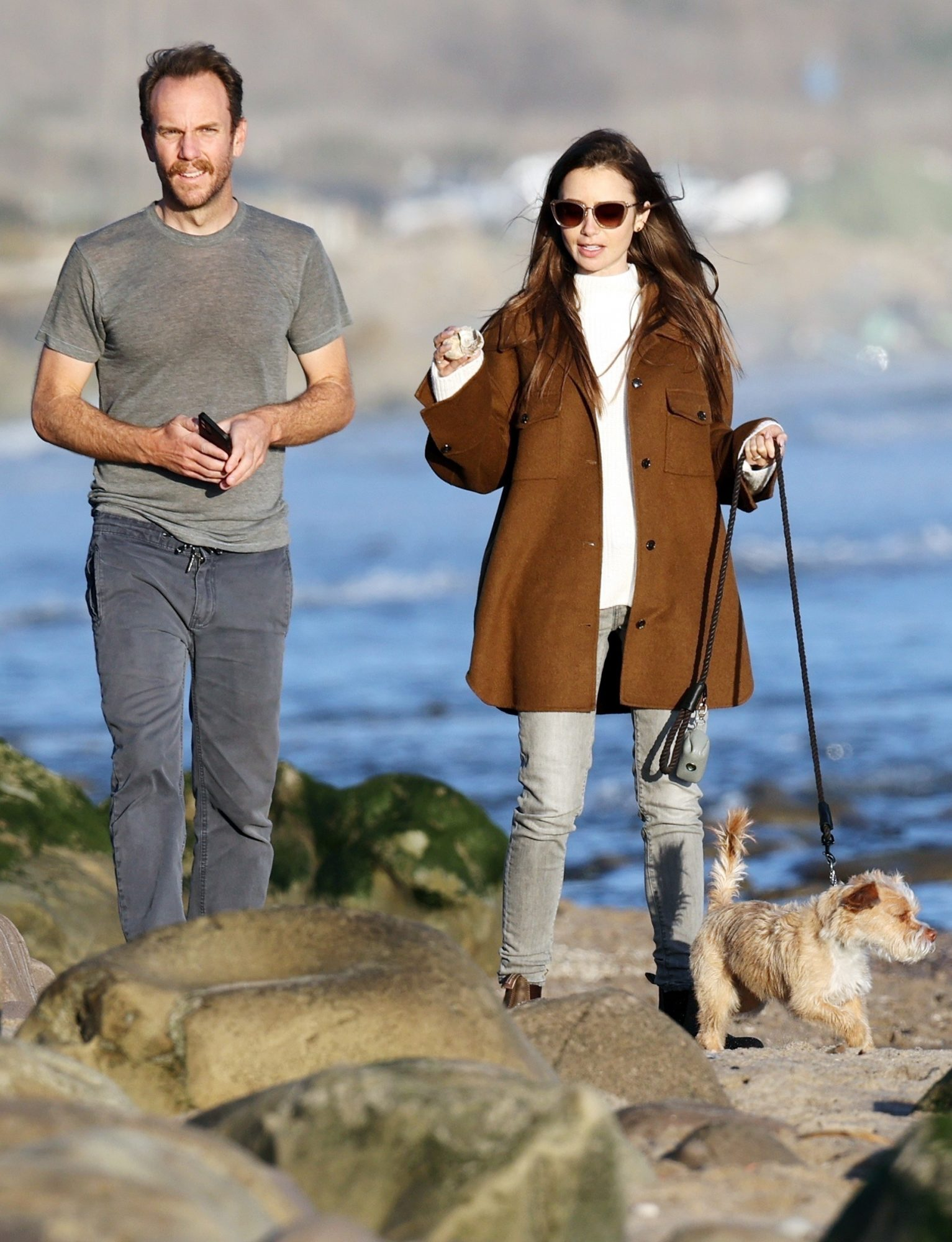 Newly engaged Lily Collins and Charlie McDowell take their dog Redford for a walk on the beach
