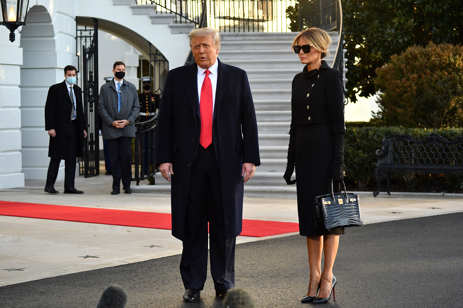 Outgoing US President Donald Trump and First Lady Melania Trump speak to the media depart the White House