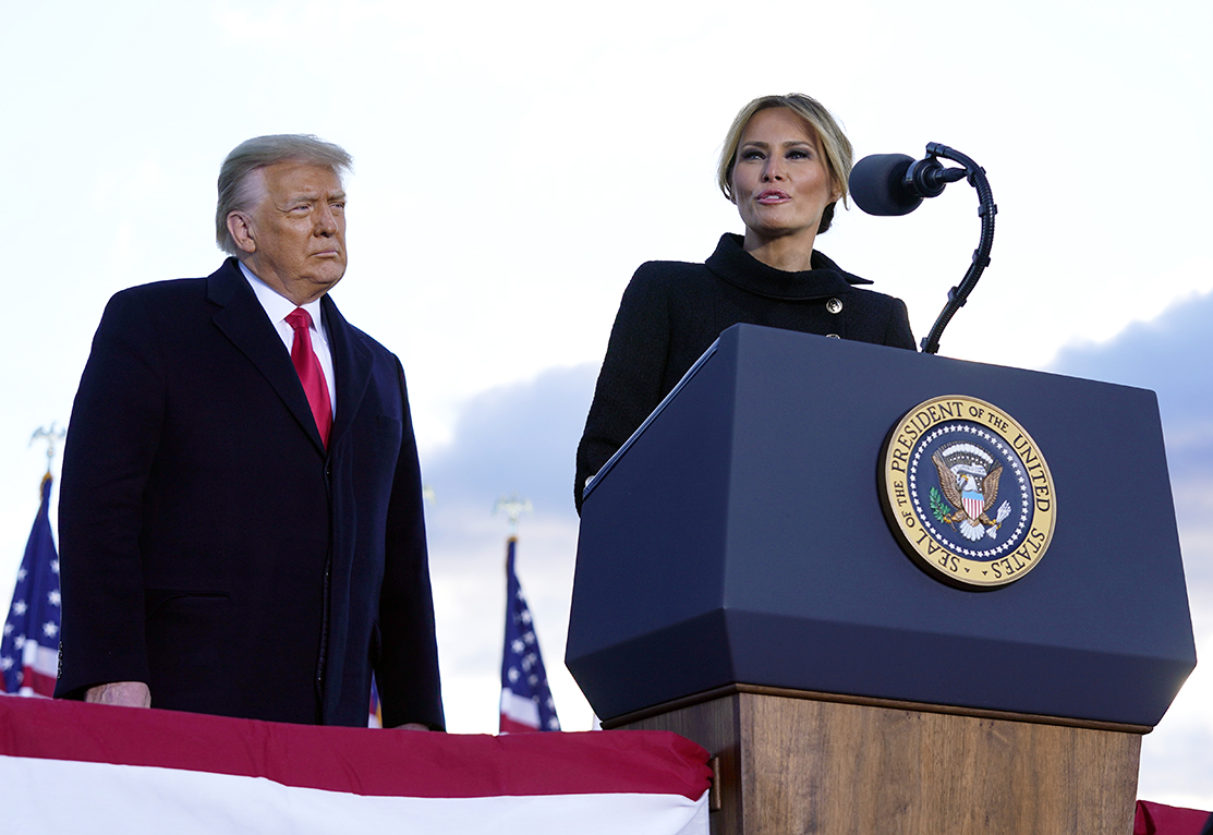 President Donald Trump listens as First Lady Melania Trump speaks before boarding Air Force One at Andrews Air Force Base, Md