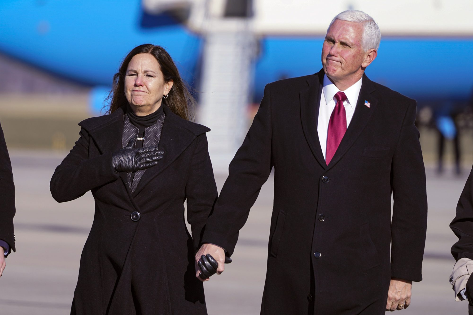 Former Vice President Mike Pence and his wife Karen walk from the plane to greet supporters after arriving back in his hometown of Columbus, Ind