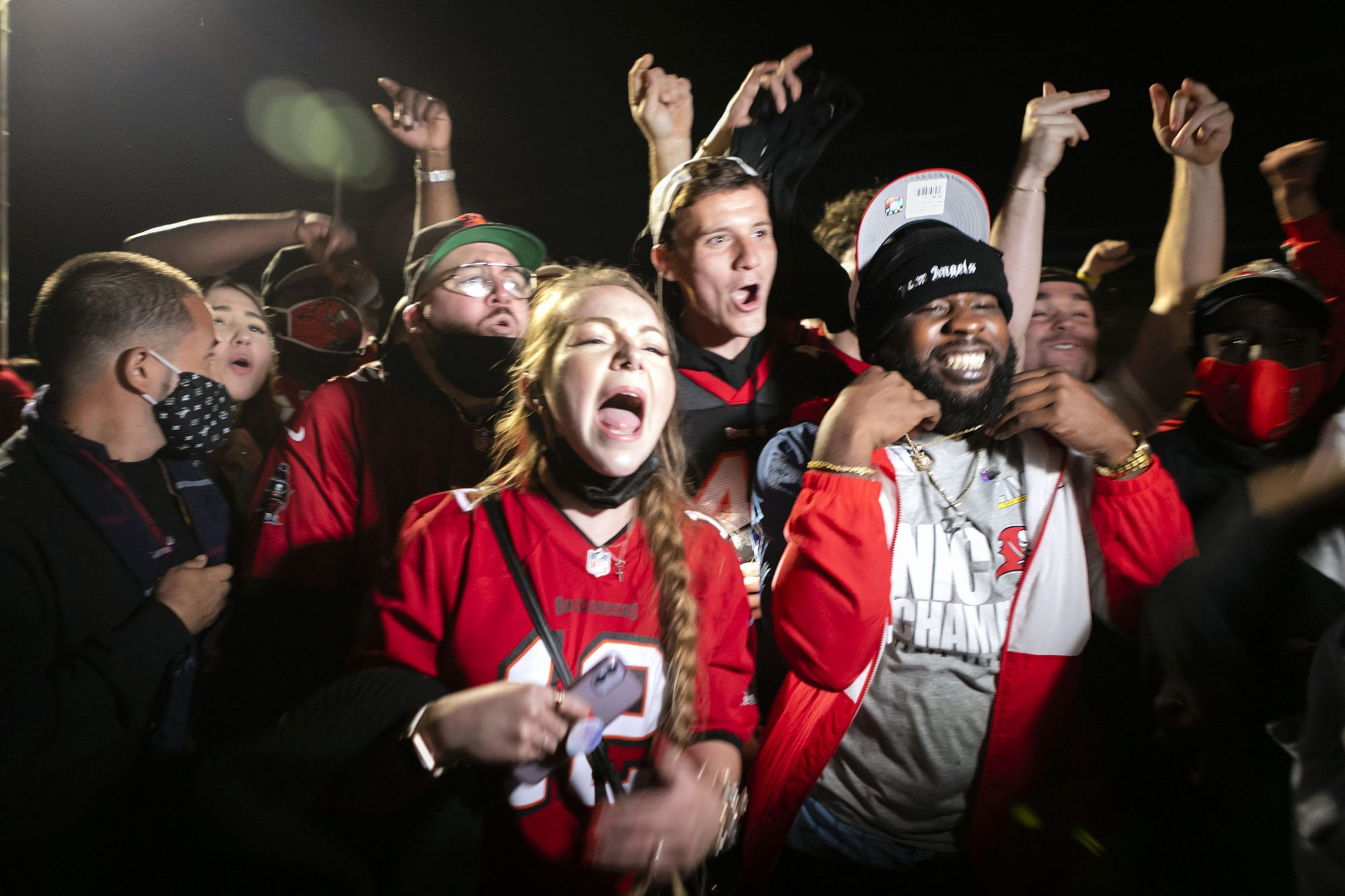 Tampa Bay Buccaneers fans celebrate their victory over the Kansas City Chiefs during Super Bowl LV in a street in downtown Tampa