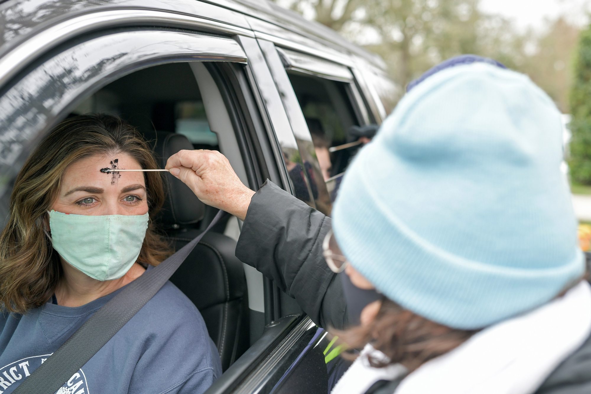 A clergy member from Munholland United Methodist Church spreads ashes on the forehead of a congregant in the drive-thru Ash Wednesday prayer and imposition of ashes on February 17, 2021 in New Orleans, Louisiana
