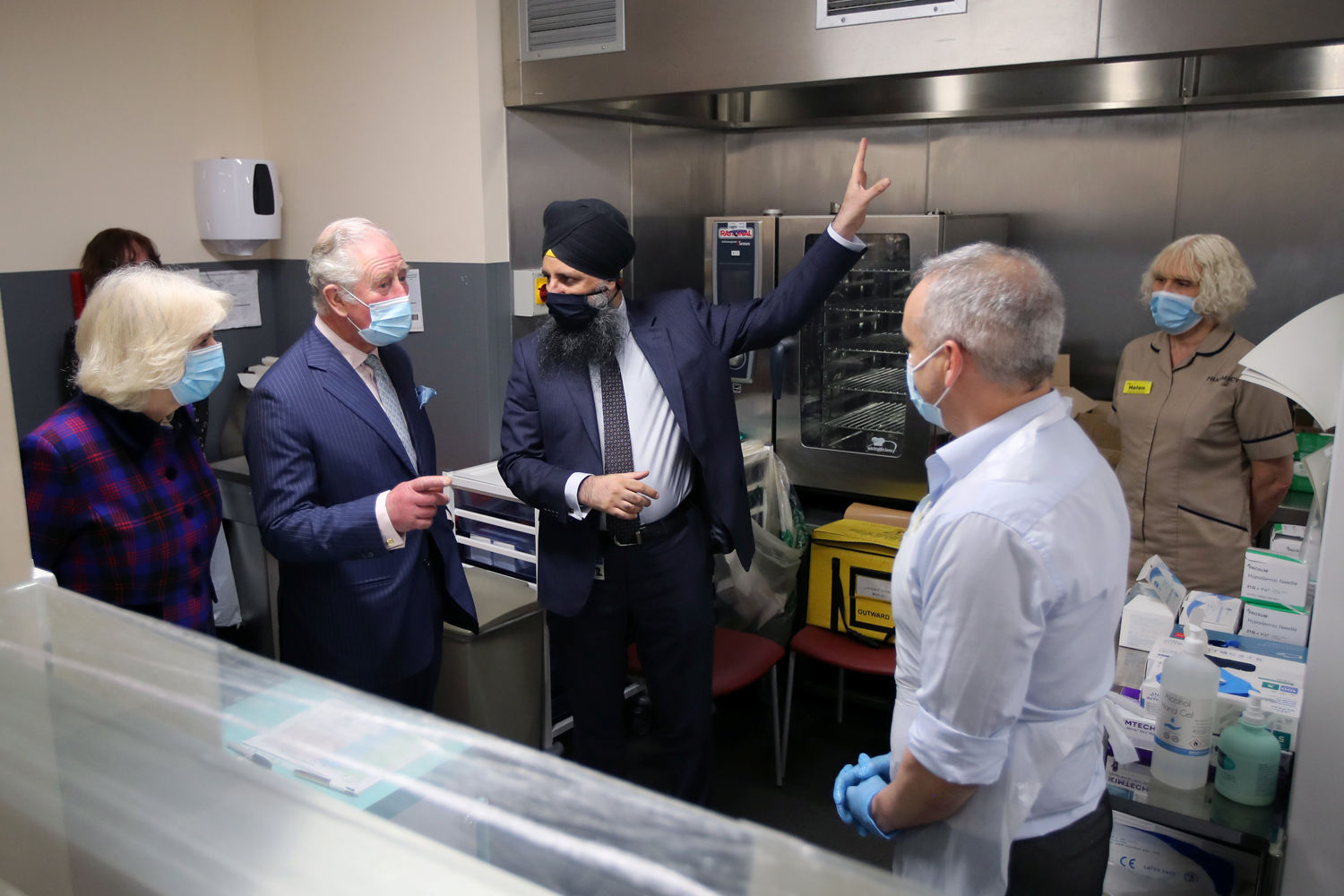 Prince Charles, Prince of Wales and Camilla, Duchess of Cornwall talk with Chief Pharmacist Inderjit Singh during a visit to The Queen Elizabeth Hospital