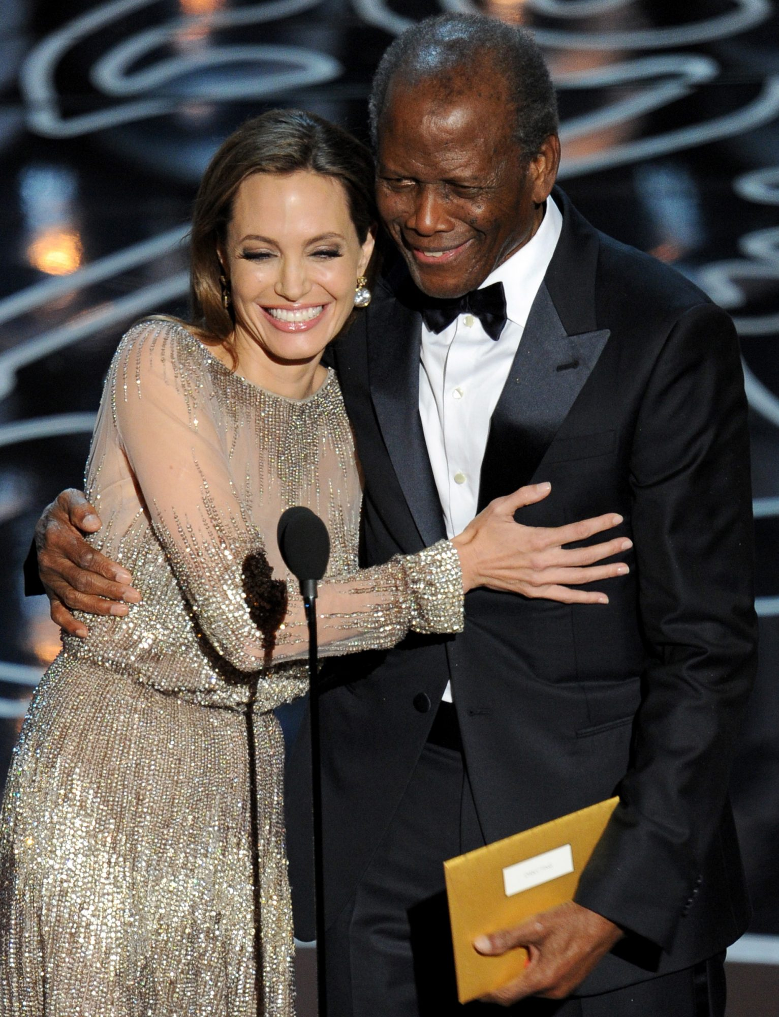 Angelina Jolie (L) and Sidney Poitier walk onstage during the Oscars at the Dolby Theatre on March 2, 2014