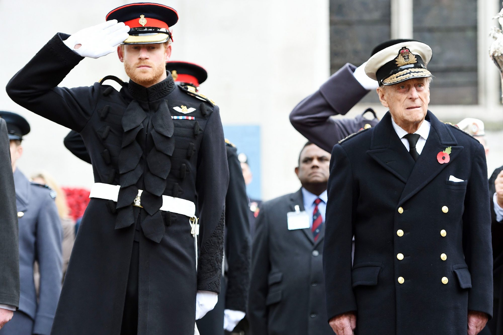 Britain's Prince Harry (L) salutes as he stands alongside his grandfather Britain's Prince Philip, Duke of Edinburgh, during their visit to the Field of Remembrance at Westminster Abbey in central London on November 10, 2016