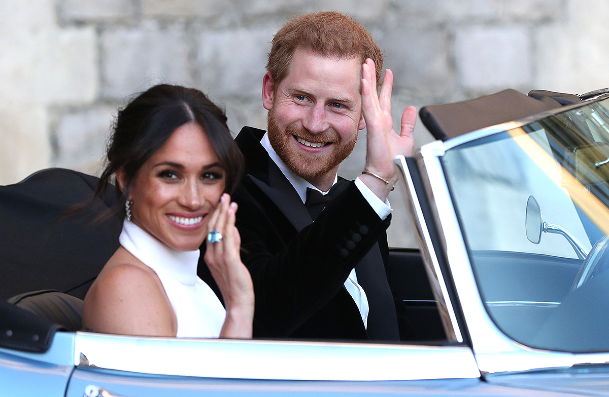 Britain's Prince Harry, Duke of Sussex, (R) and Meghan Markle, Duchess of Sussex, (L) leave Windsor Castle in Windsor on May 19, 2018 in an E-Type Jaguar after their wedding to attend an evening reception at Frogmore House