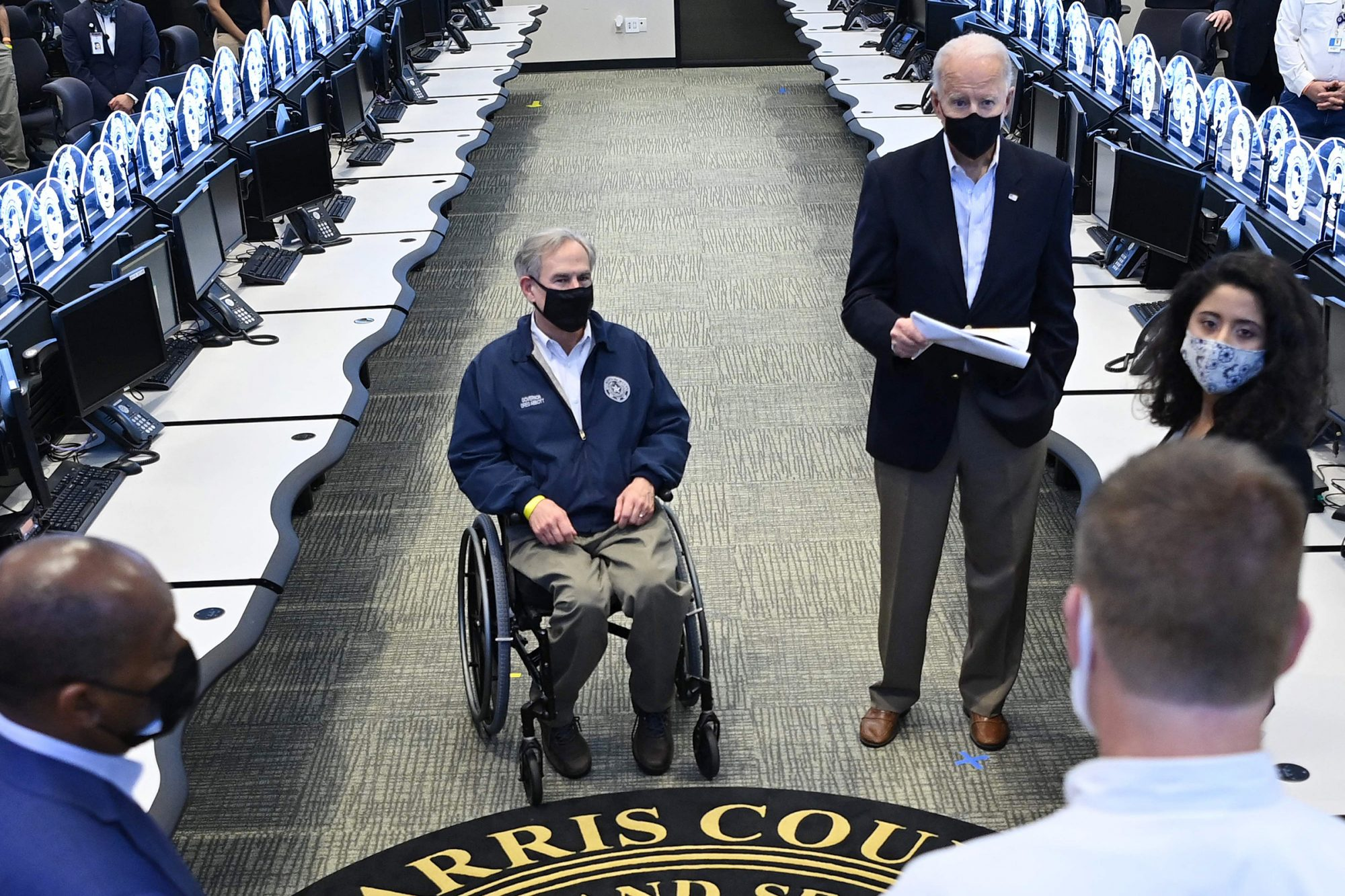 President Joe Biden and Texas Governor Greg Abbott (L) listen to officials at the Harris County Emergency Operations Center in Houston, Texas on February 26, 2021