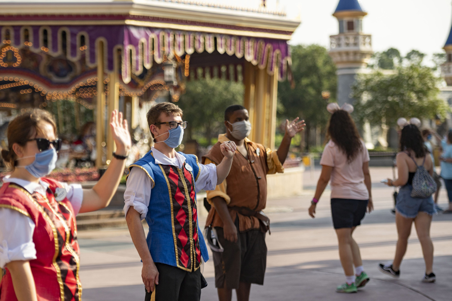In this handout photo provided by Walt Disney World Resort, Disney cast members welcome guests to Magic Kingdom Park at Walt Disney World Resort