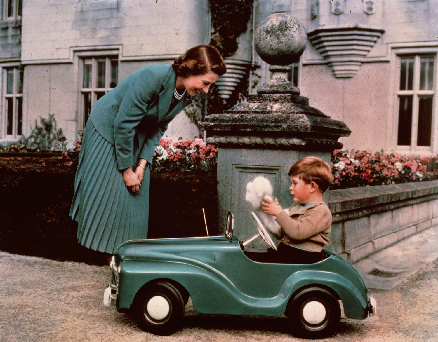 Princess Elizabeth watching her son Prince Charles playing in his toy car