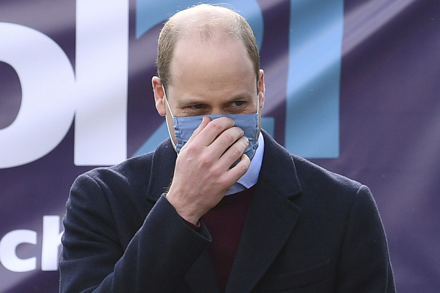 Prince William adjusts his face mask during a visit with Kate, Duchess of Cambridge to School21