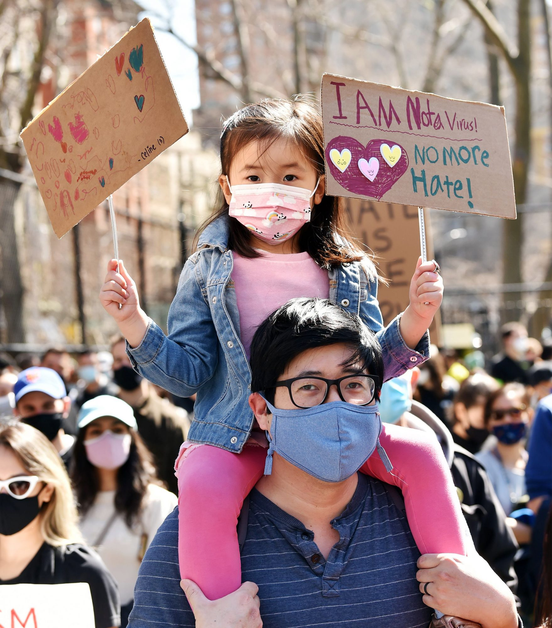 A man holds a child on his shoulders at the Rally Against Hate to protest the recent violence aimed at the Asian American community at Columbus Park
