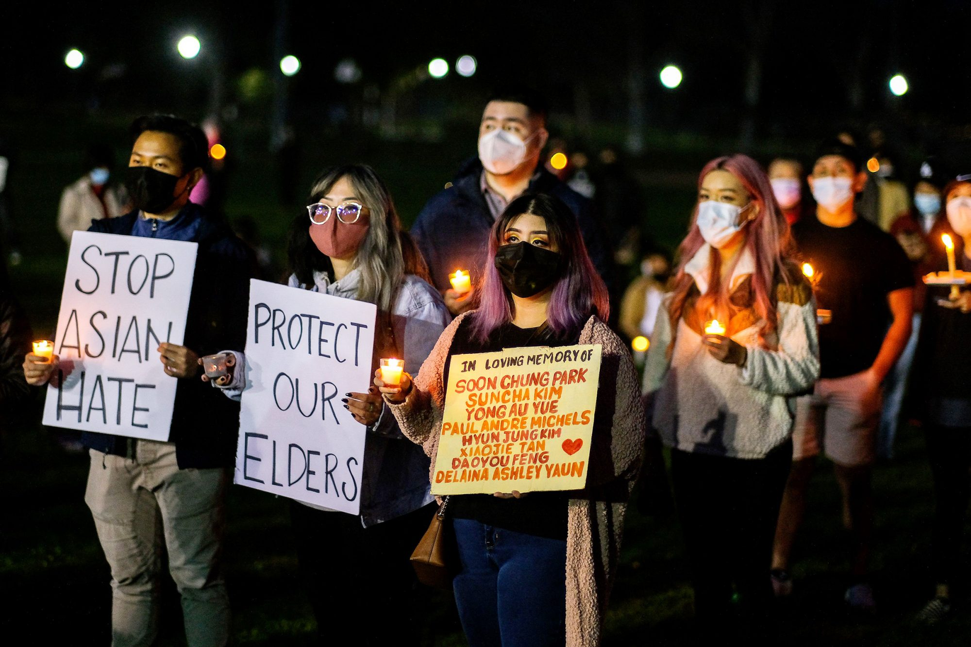 People holding candles and anti-hate signs take part in a candlelight vigil in standing up against Asian American Pacific Islander (AAPI) hate and violence, at Almansor Park in Alhambra, California, on March 20, 2021.
