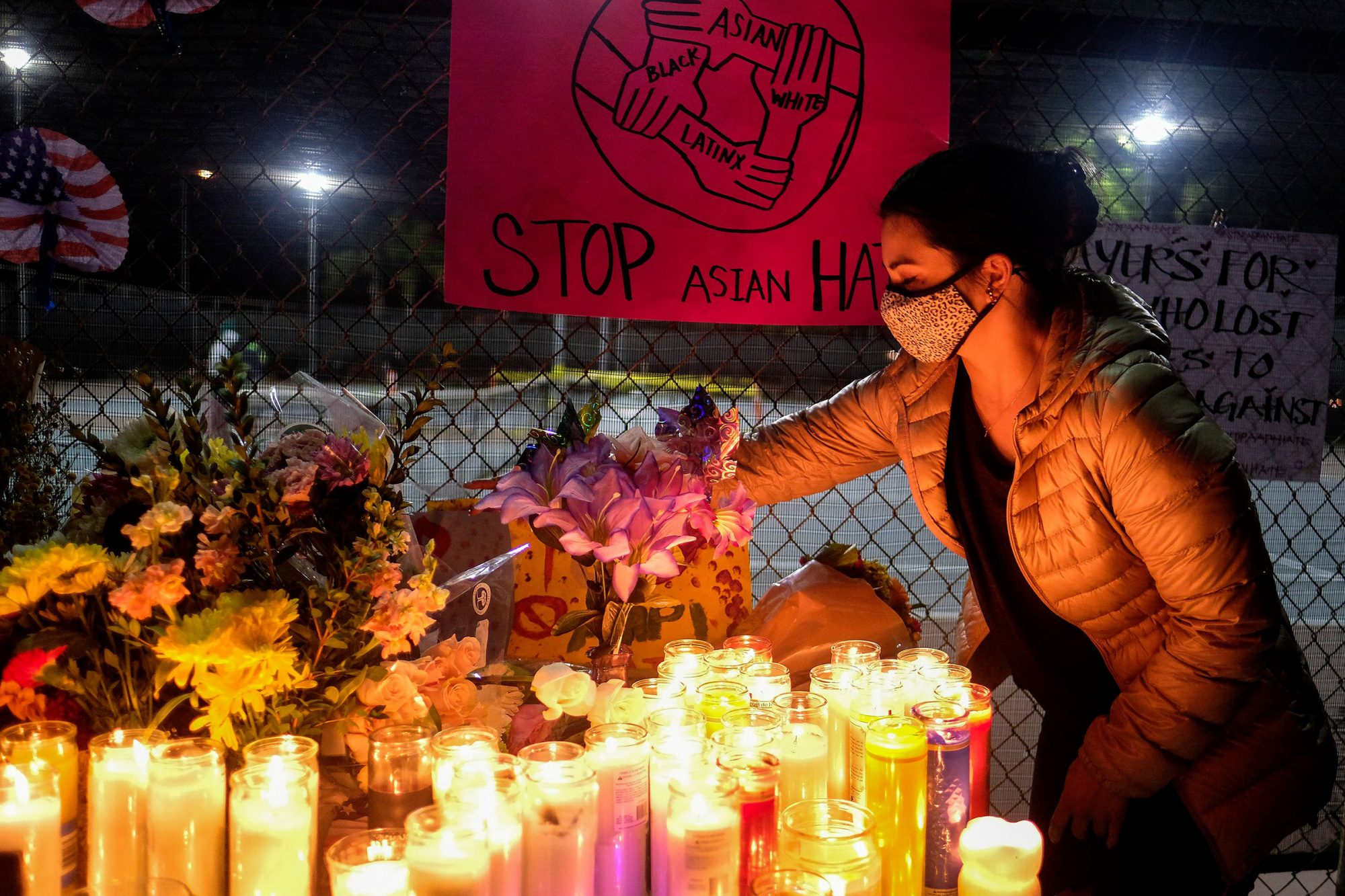 A woman places an anti-hate sign during a candlelight vigil in standing up against Asian American Pacific Islander (AAPI) hate and violence, at Almansor Park in Alhambra, California, on March 20, 2021