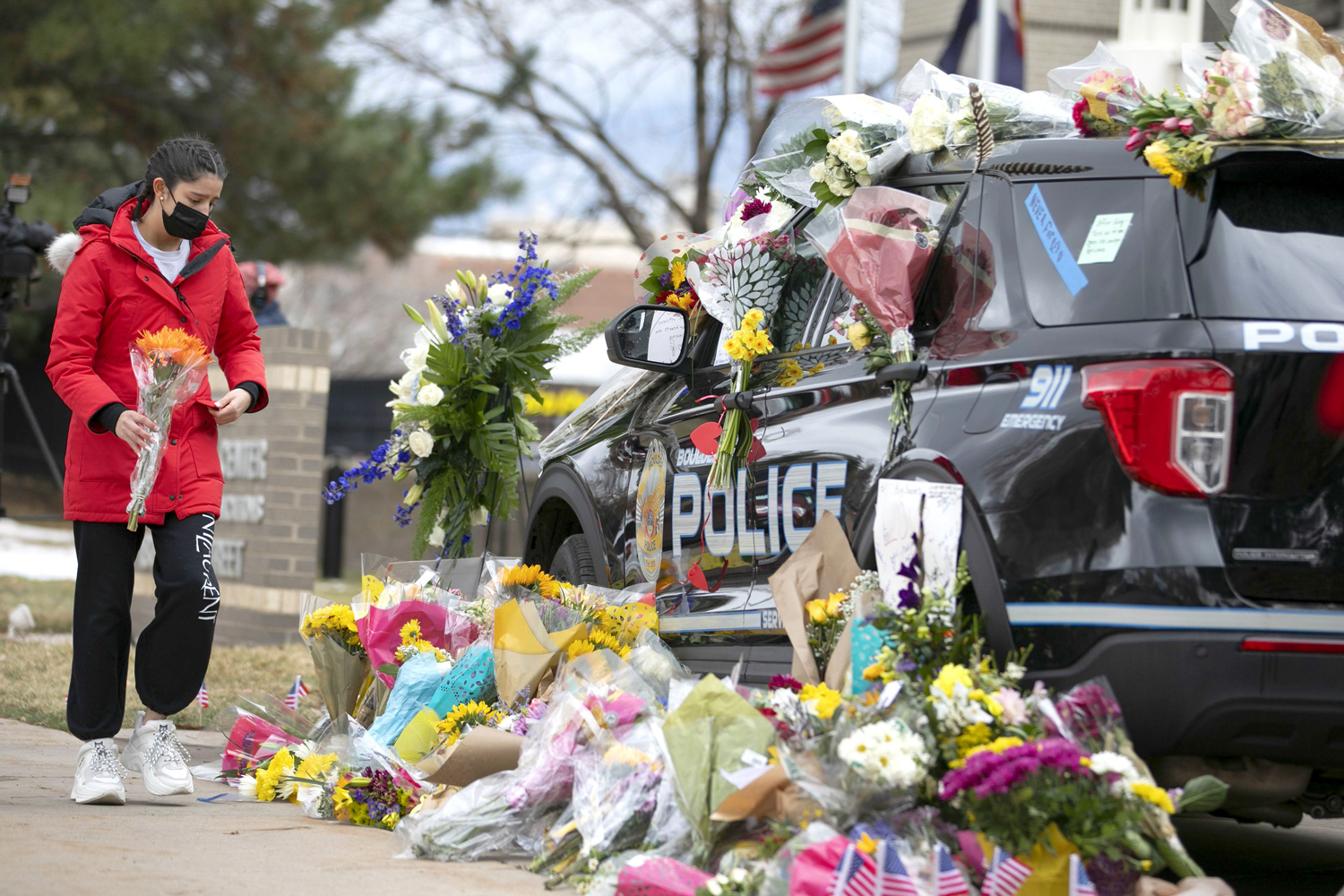 A woman prepares to lay flowers at a makeshift memorial on a police vehicle outside police headquarters