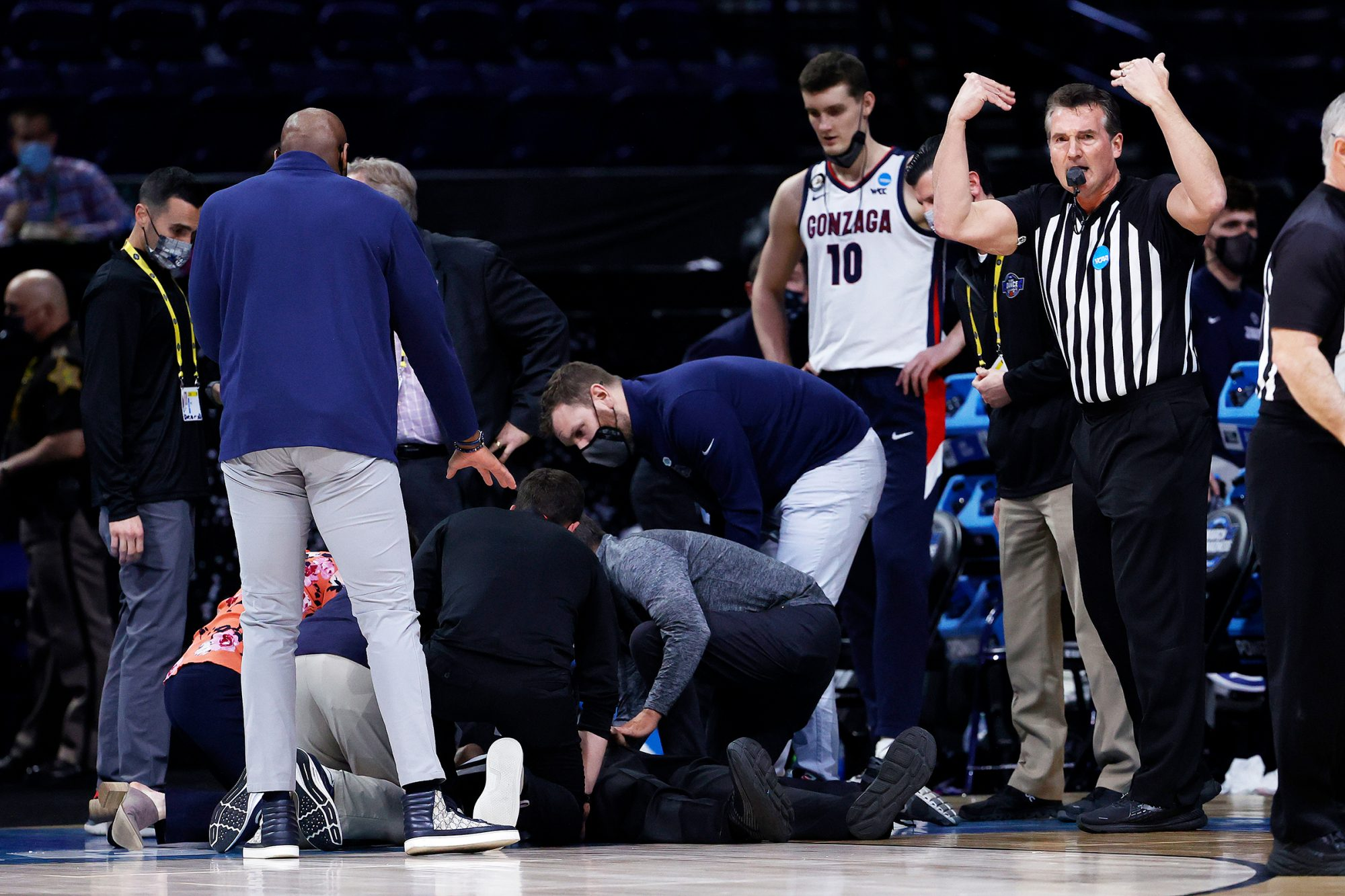 Referee Bert Smith is tended to by training staff and medical personnel after collapsing during the first half of the Elite Eight round game between the USC Trojans and the Gonzaga Bulldogs during the 2021 NCAA Men's Basketball Tournament at Lucas Oil Stadium on March 30, 2021