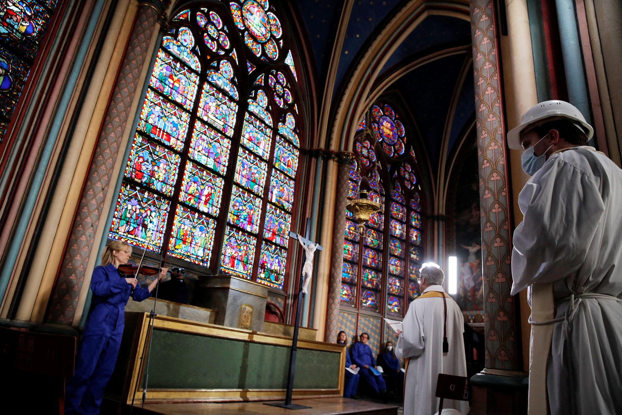 Notre Dame rector Patrick Chauvet (2ndR) attends a ceremony as part of Maundy Thursday, in Notre-Dame cathedral in Paris, on April 1, 2021, almost two years after a massive fire ravaged the Gothic cathedral
