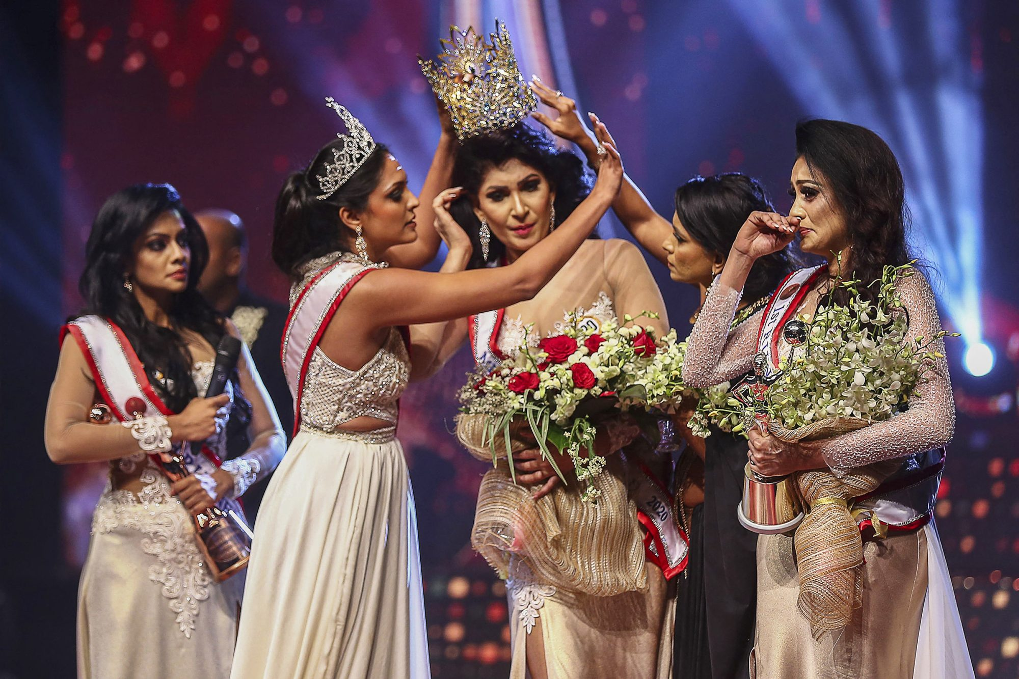 In this photograph taken on April 4, 2021, winner of Mrs. Sri Lanka 2020 Caroline Jurie (2-L) removes the crown of 2021 winner Pushpika de Silva (C) as she is disqualified by the jurie over the accusation of being divorced, at a beauty pageant for married women in Colombo