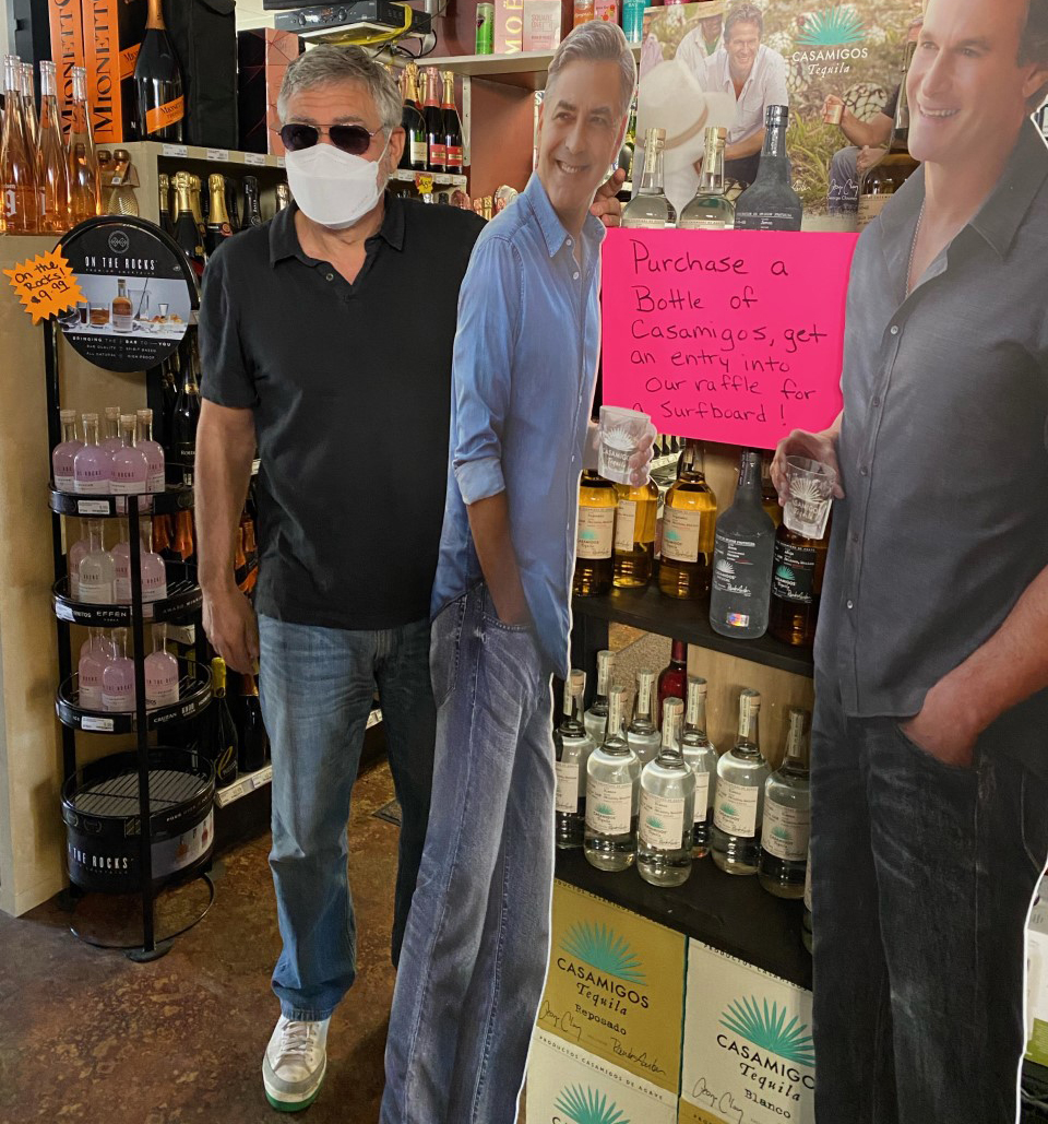 George Clooney poses with Casamigos bottles and cutout