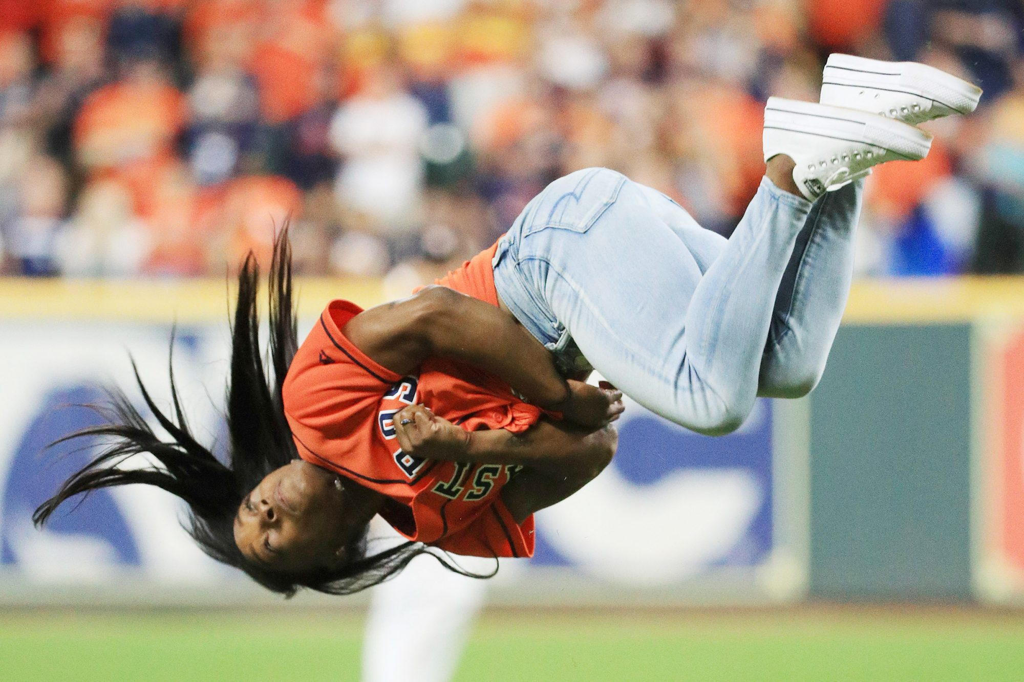 Simone Biles performs a flip after throwing out the ceremonial first pitch prior to Game Two of the 2019 World Series between the Houston Astros and the Washington Nationals at Minute Maid Park on October 23, 2019