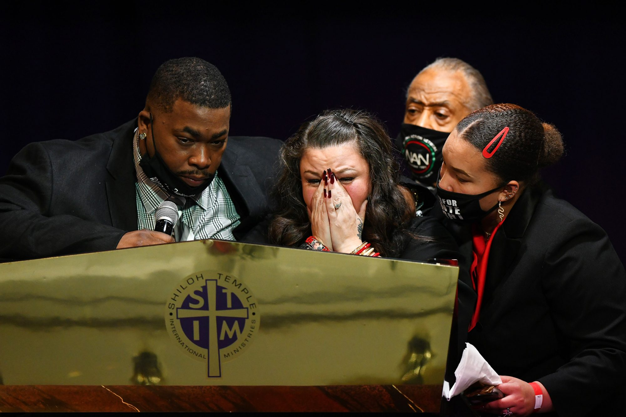 Father Arbuey Wright (L) and mother Katie Wright (2L) give remarks alongside sister Diamond Wright (R) and Rev Al Sharpton during a funeral held for Daunte Wright
