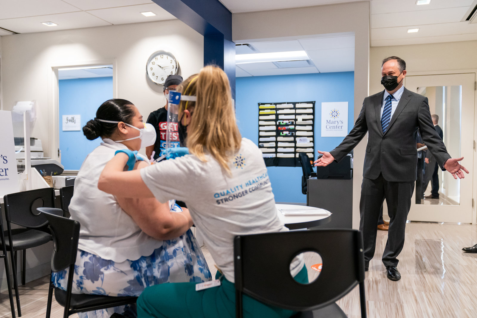 Second Gentleman Douglas Emhoff looks on as Jessica Palacios receives a COVID-19 vaccine from nurse Eva Sweeny Tuesday, March 30, 2021, at Mary's Center in Silver Spring, Maryland.