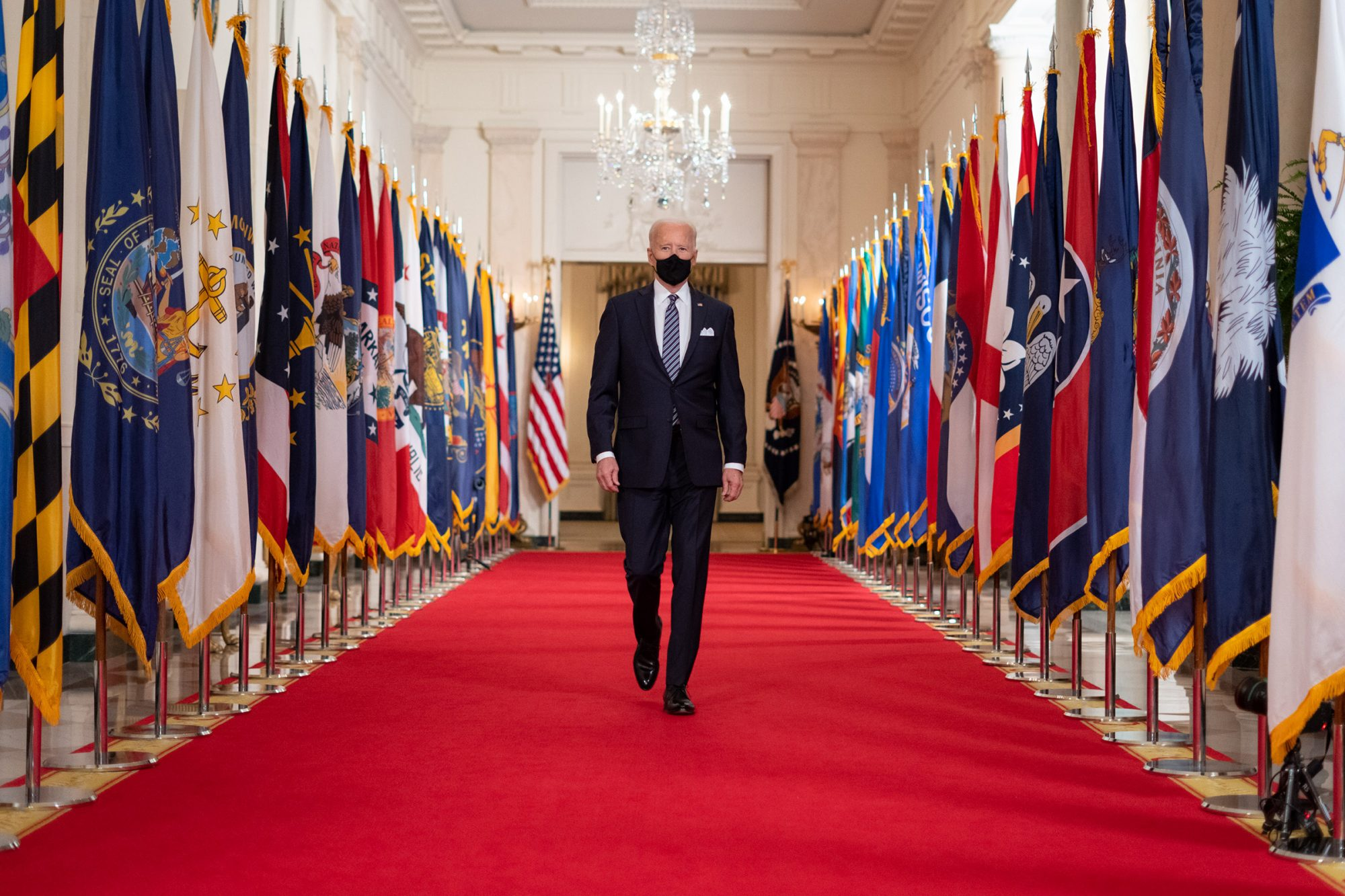 President Joe Biden walks from the State Dining Room of the White House to a podium in the Cross Hall of the White House Thursday, March 11, 2021, to deliver remarks on the one year anniversary of the COVID-19 Shutdown.