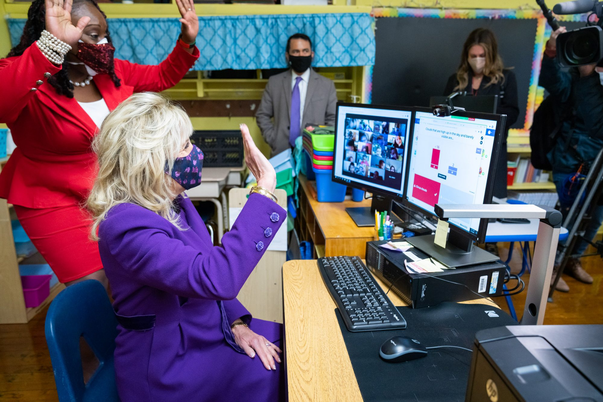 First Lady Jill Biden waves at second grade students who are attending class virtually Monday, March 15, 2021, during her tour at the Samuel Smith Elementary School in Burlington, New Jersey.