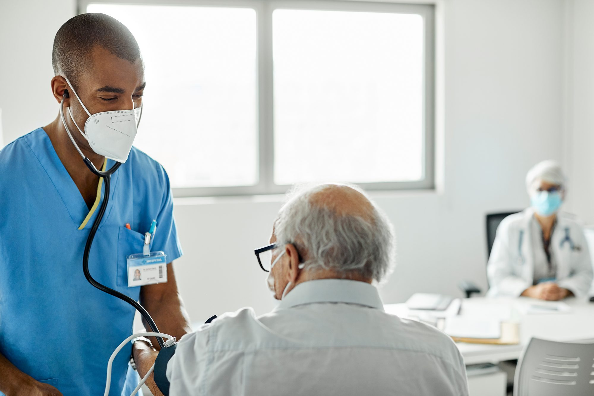 Nurse checking patient in clinic during COVID-19