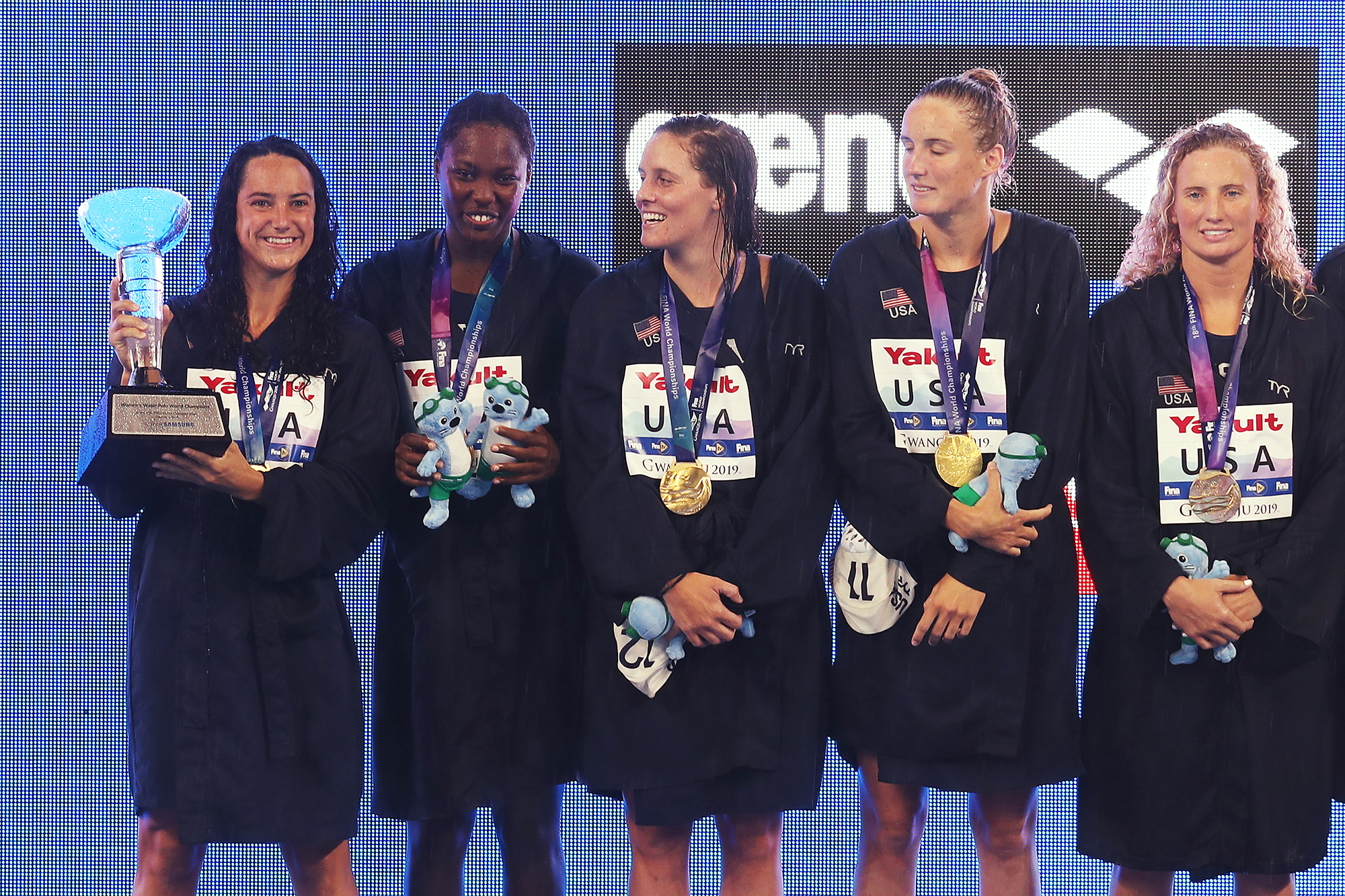 Margaret Steffens (L) of the United States poses with the winner's trophy alongside her teammates during the medal ceremony for the Women's Water Polo