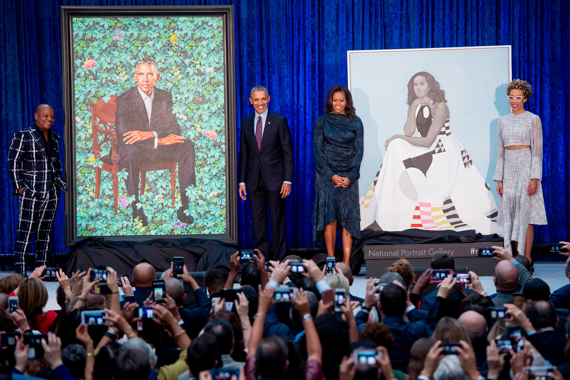 Former US President Barack Obama and First Lady Michelle Obama stand before their portraits and respective artists, Kehinde Wiley (L) and Amy Sherald (R), after an unveiling at the Smithsonian's National Portrait Gallery in Washington, DC, February 12, 2018